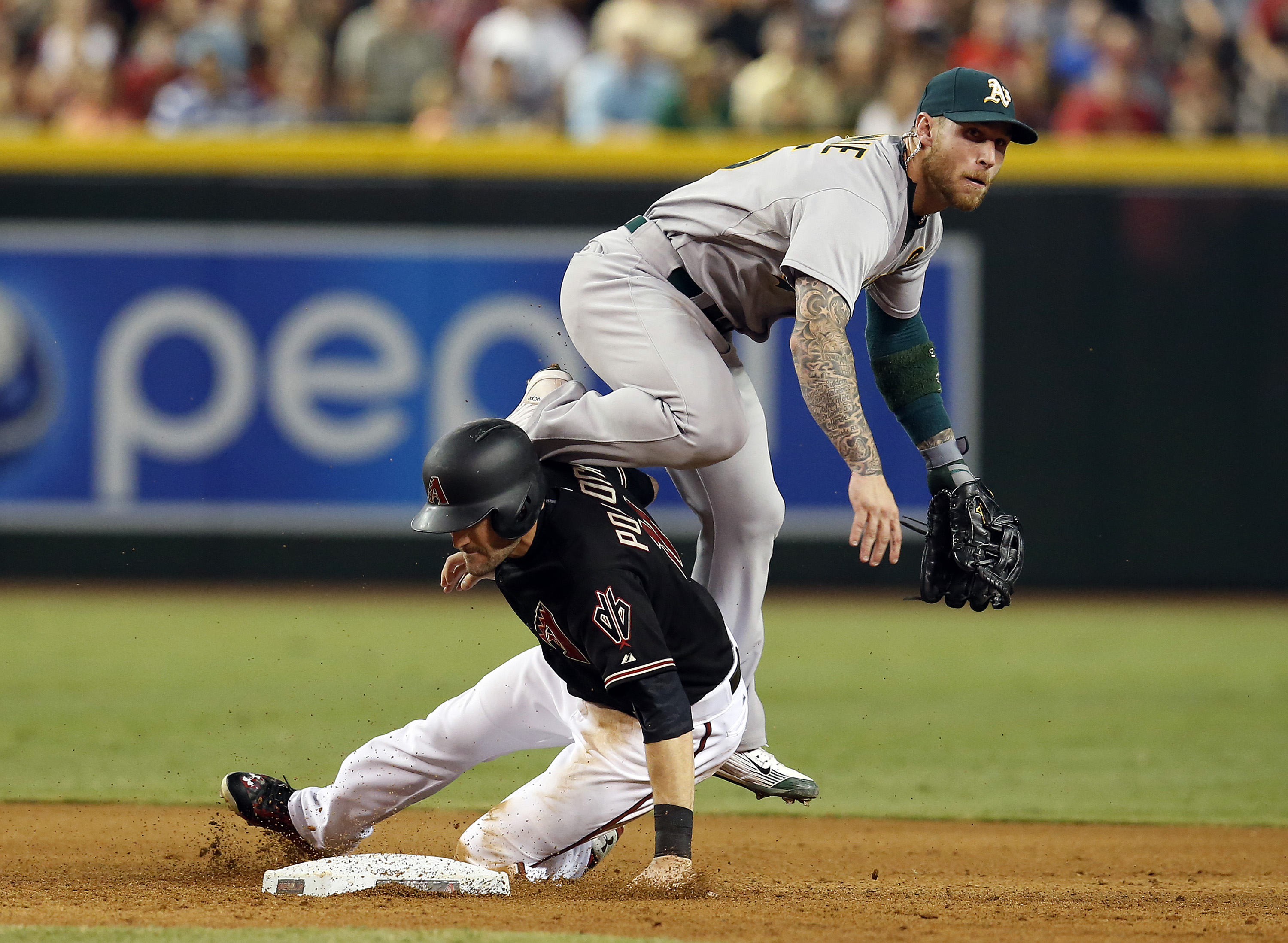 Oakland Athletics second baseman Brett Lawrie, right, turns the double play while avoiding Arizona Diamondbacks A.J. Pollock on a ball hit by Paul Goldschmidt in the fifth inning during a baseball game, Saturday, Aug. 29, 2015, in Phoenix. (AP Photo/Rick