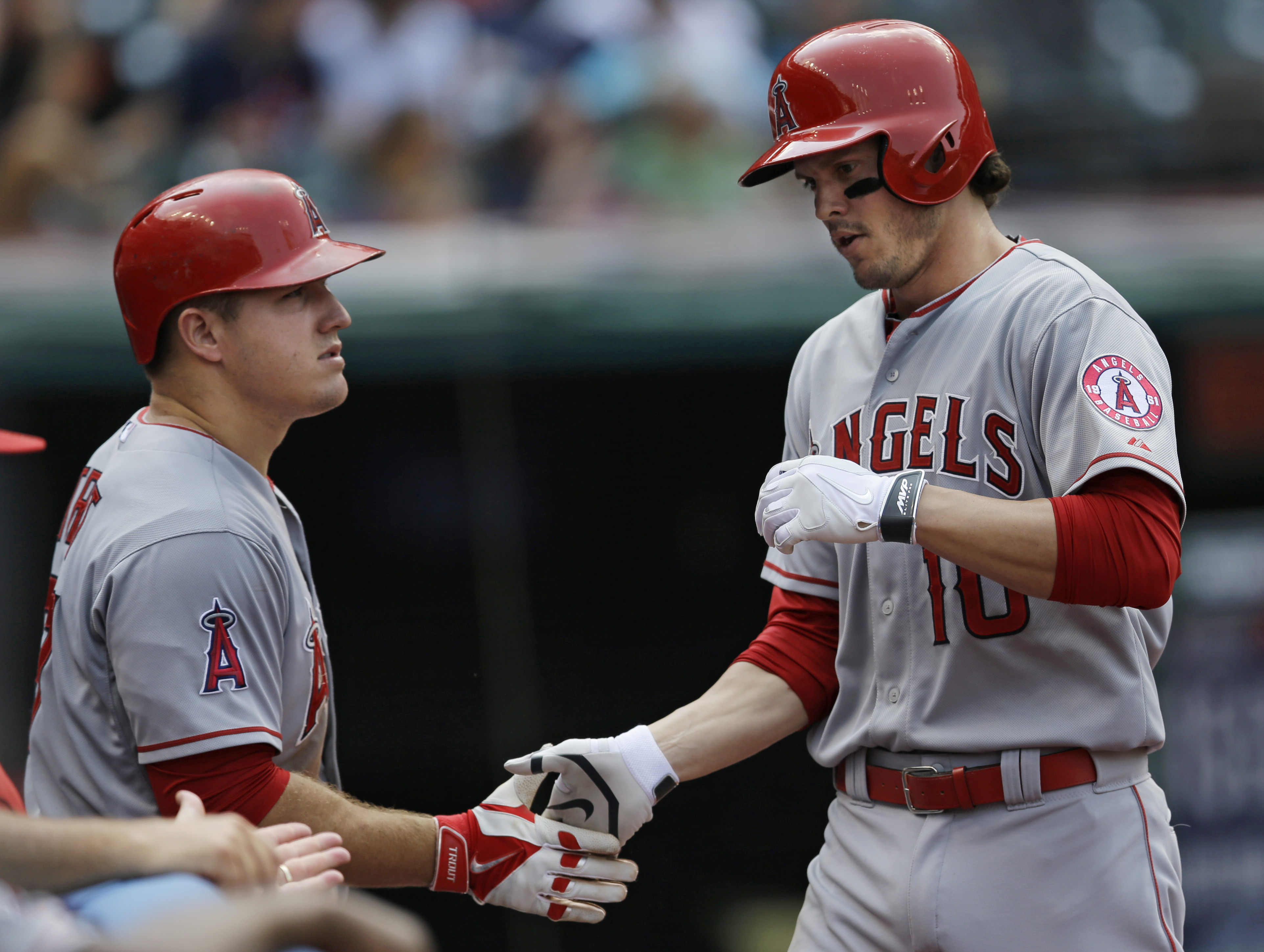 Los Angeles Angels' Grant Green, right, is congratulated by Mike Trout after hitting a solo home run off Cleveland Indians starting pitcher Josh Tomlin in the sixth inning of a baseball game, Sunday, Aug. 30, 2015, in Cleveland. (AP Photo/Tony Dejak)
