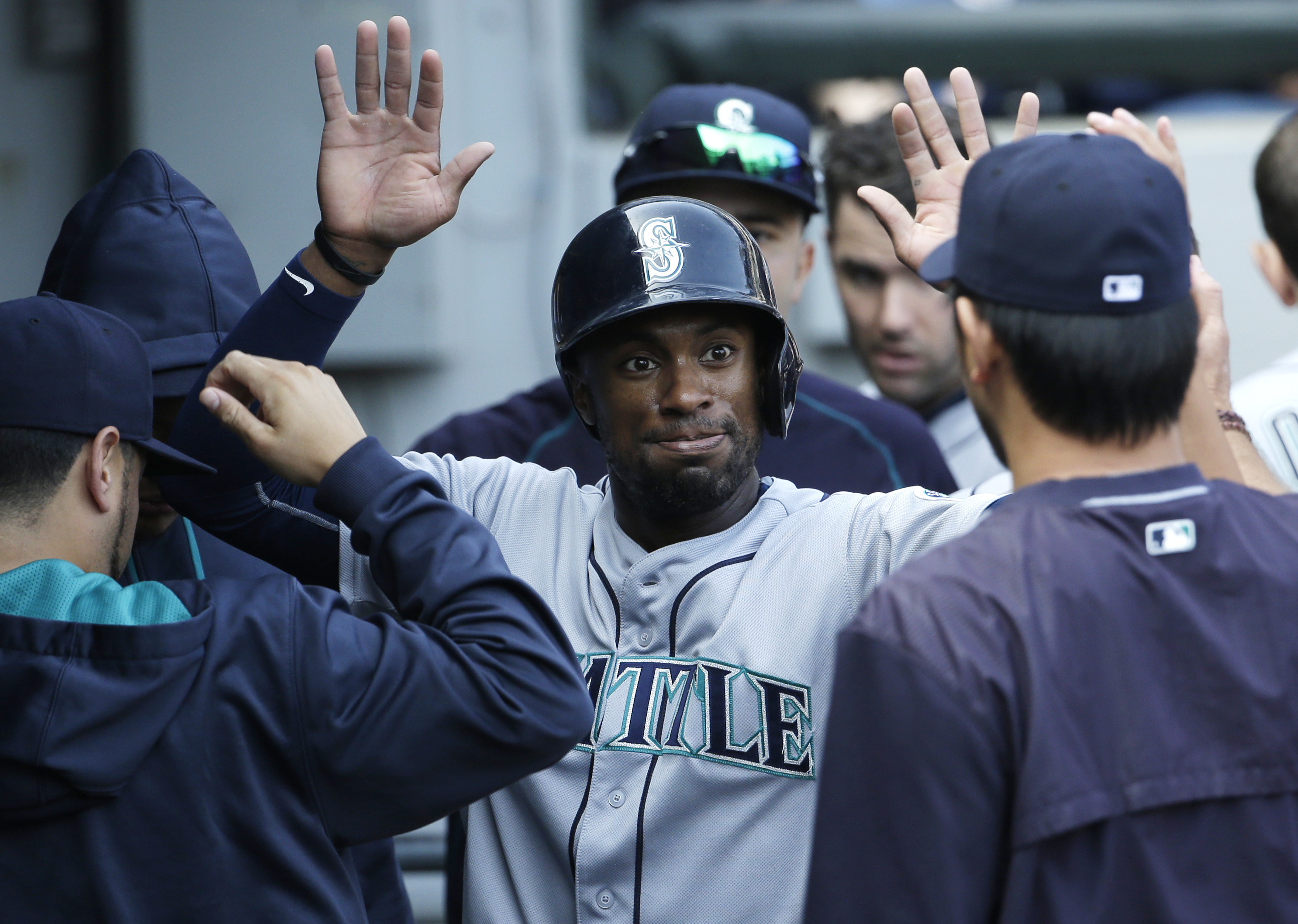 Seattle Mariners' Austin Jackson celebrates with teammates after scoring on a single by Kyle Seager during the eighth inning of a baseball game against the Chicago White Sox, Sunday, Aug. 30, 2015, in Chicago. (AP Photo/Nam Y. Huh)
