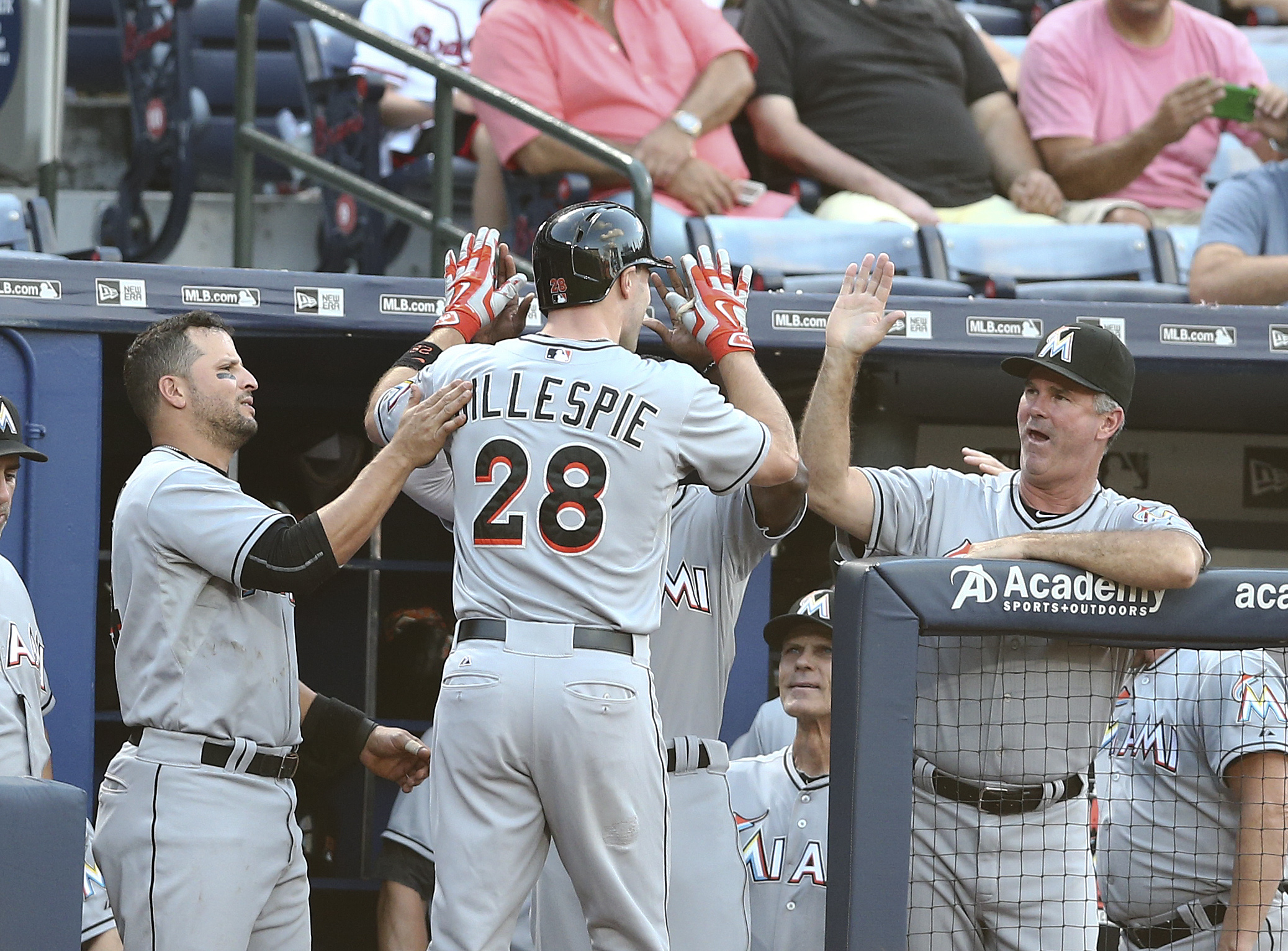 Miami Marlins center fielder Cole Gillespie (28) is greeted at the dugout entrance by Miami Marlins third baseman Martin Prado, left, and manager Dan Jennings after hitting a solo home run in the second inning of a baseball game against the Atlanta Braves