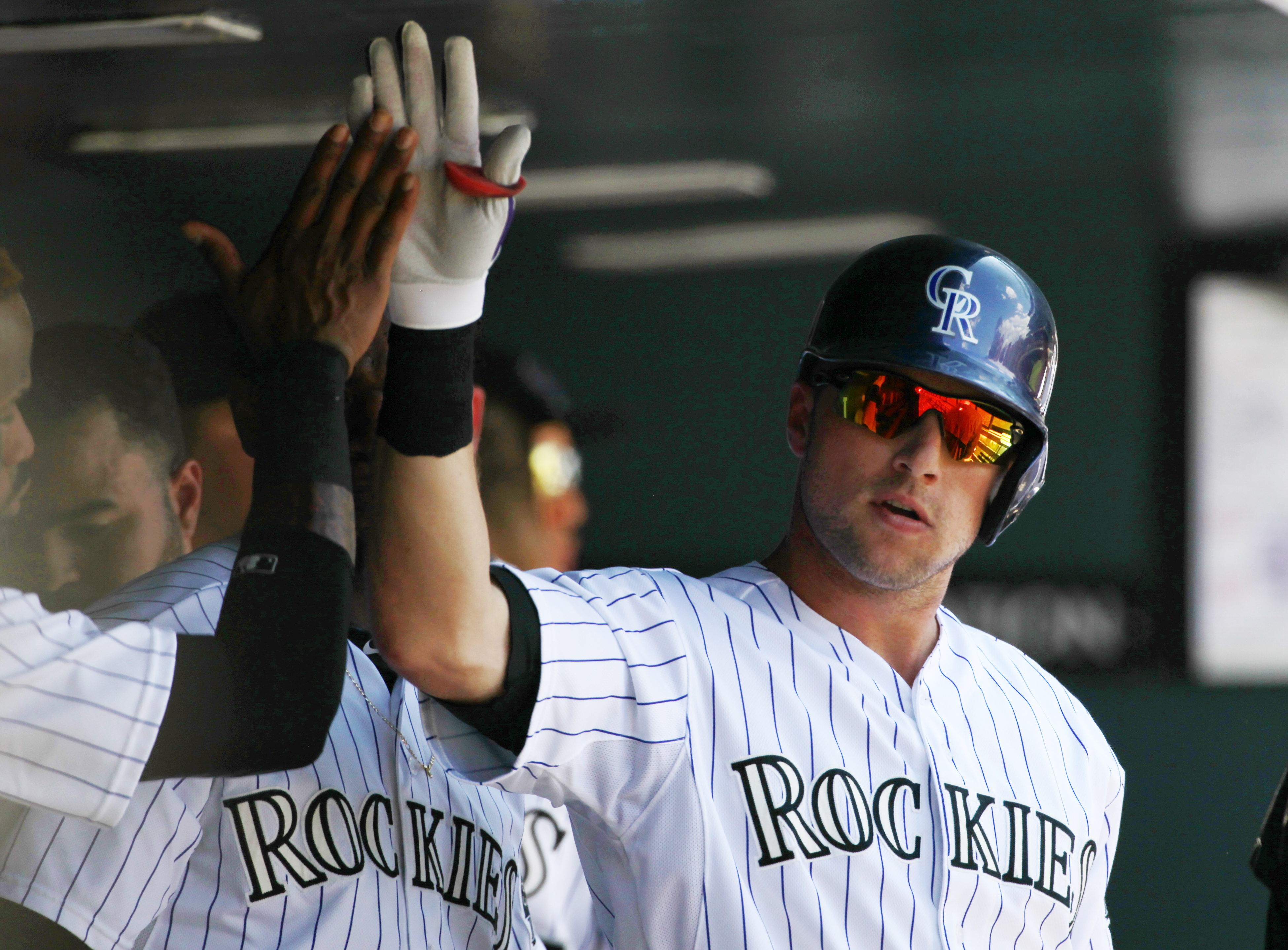 Colorado Rockies' Kyle Parker celebrates scoring a run with teammates in the dugout during the fifth inning of the first game of a baseball double header against the Arizona Diamondbacks Tuesday, Sept. 1, 2015, in Denver. (AP Photo/Jack Dempsey)