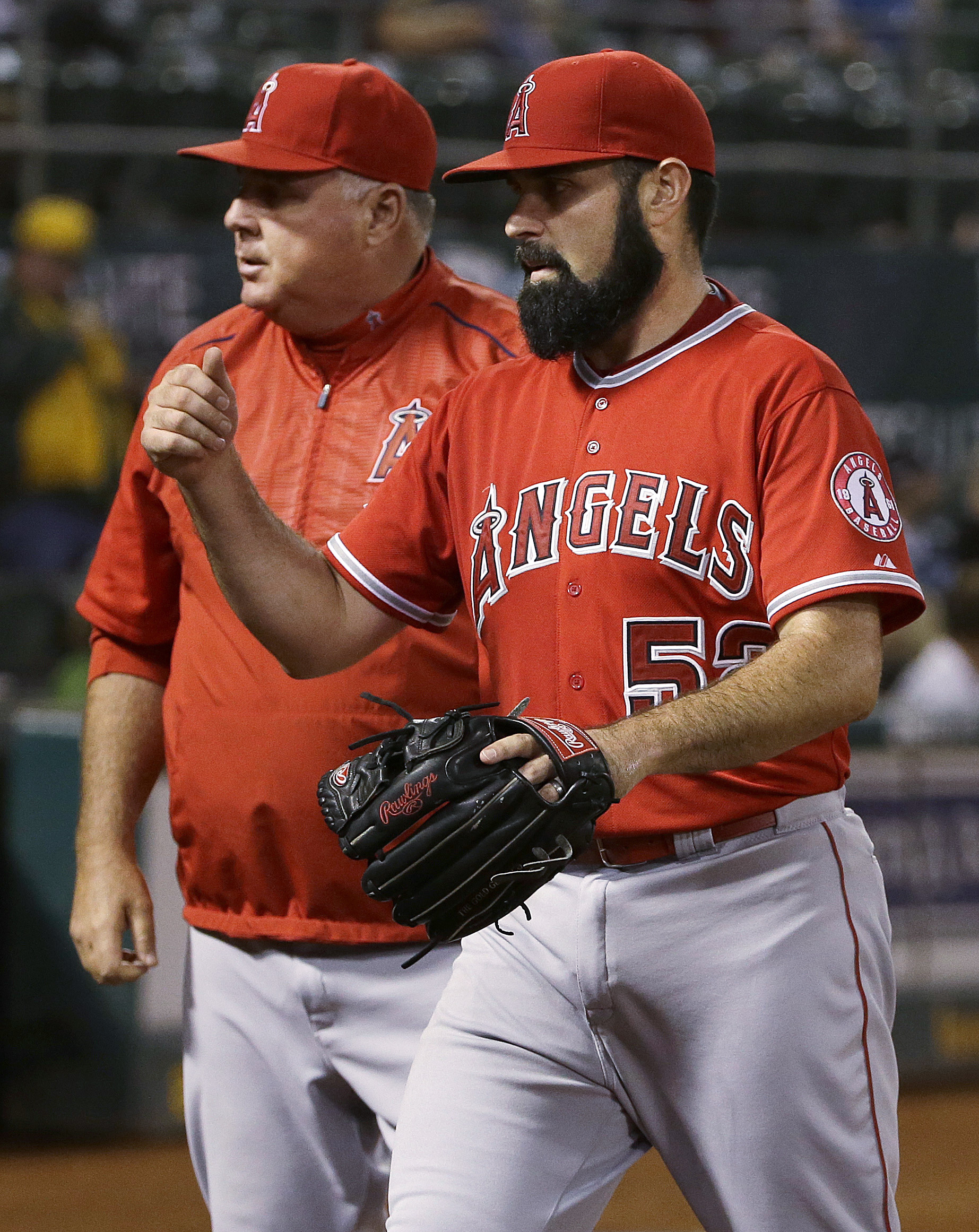 Los Angeles Angels pitcher Matt Shoemaker (52) walks toward the dugout next to manager Mike Scioscia after the seventh inning of a baseball game against the Oakland Athletics on Tuesday, Sept. 1, 2015, in Oakland, Calif. (AP Photo/Jeff Chiu)