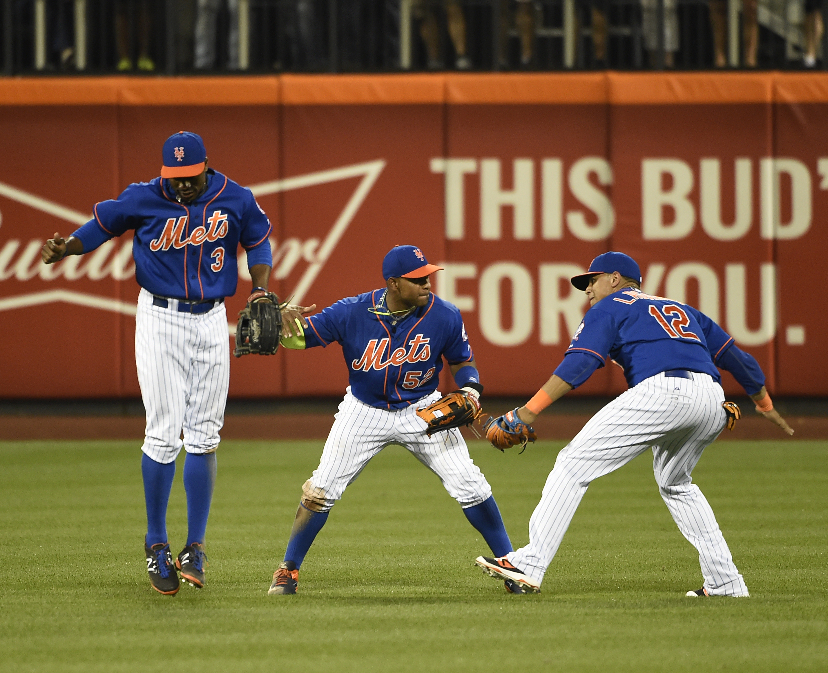 New York Mets' Curtis Granderson (3),  Yoenis Cespedes (52) and Juan Lagares celebrate the Mets' 9-4 win over the Philadelphia Phillies in a baseball game Wednesday, Sept. 2, 2015, in New York. (AP Photo/Kathy Kmonicek)