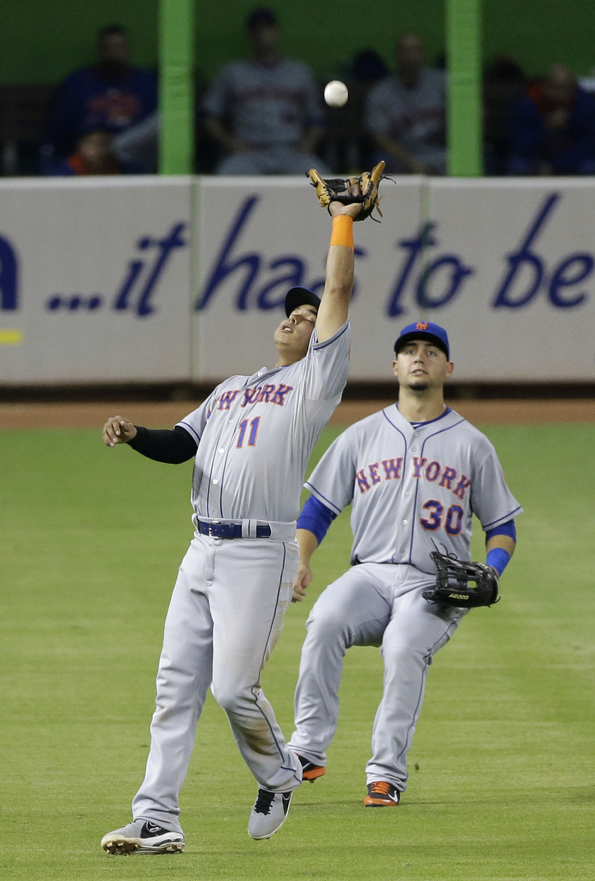 New York Mets shortstop Ruben Tejada (11) catches a ball hit by Miami Marlins' Dee Gordon as left fielder Michael Conforto (30) backs him up during the fourth inning of a baseball game, Friday, Sept. 4, 2015, in Miami. (AP Photo/Wilfredo Lee)