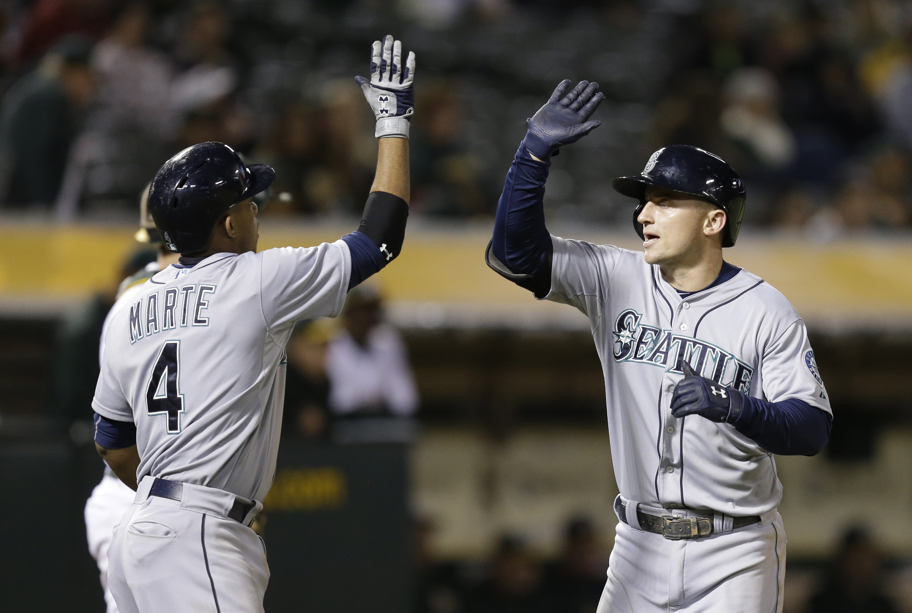 Seattle Mariners' Kyle Seager, right, celebrates with Ketel Marte (4) after hitting a two-run home run off Oakland Athletics' Drew Pomeranz in the ninth inning of a baseball game Friday, Sept. 4, 2015, in Oakland, Calif. (AP Photo/Ben Margot)