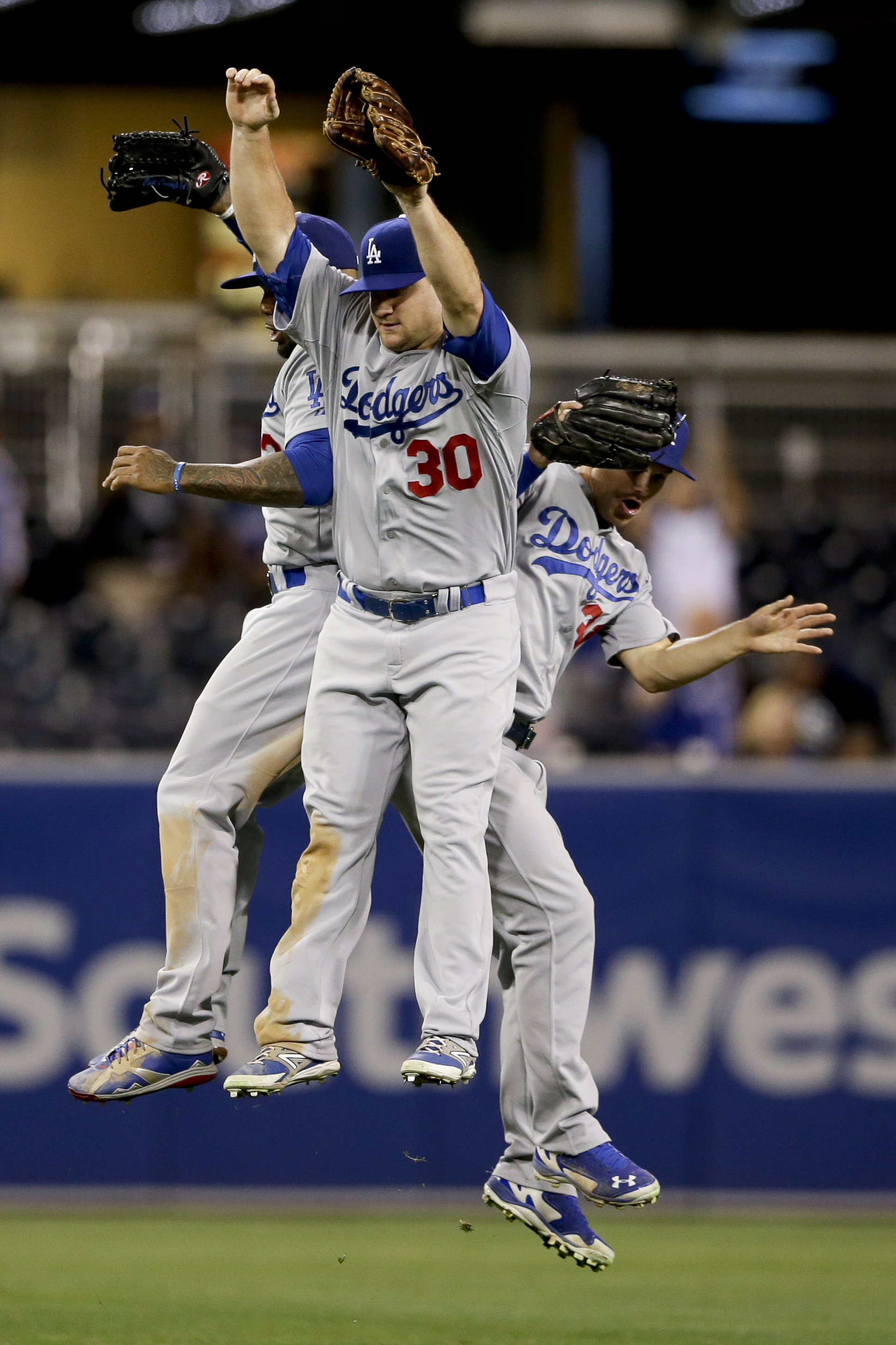 Los Angeles Dodgers left fielder Scott Schebler, center, celebrates with teammates center fielder Joc Pederson, right, and left fielder Carl Crawford, left, after their defeat of the San Diego Padres in a baseball game Friday, Sept. 4, 2015 in San Diego.