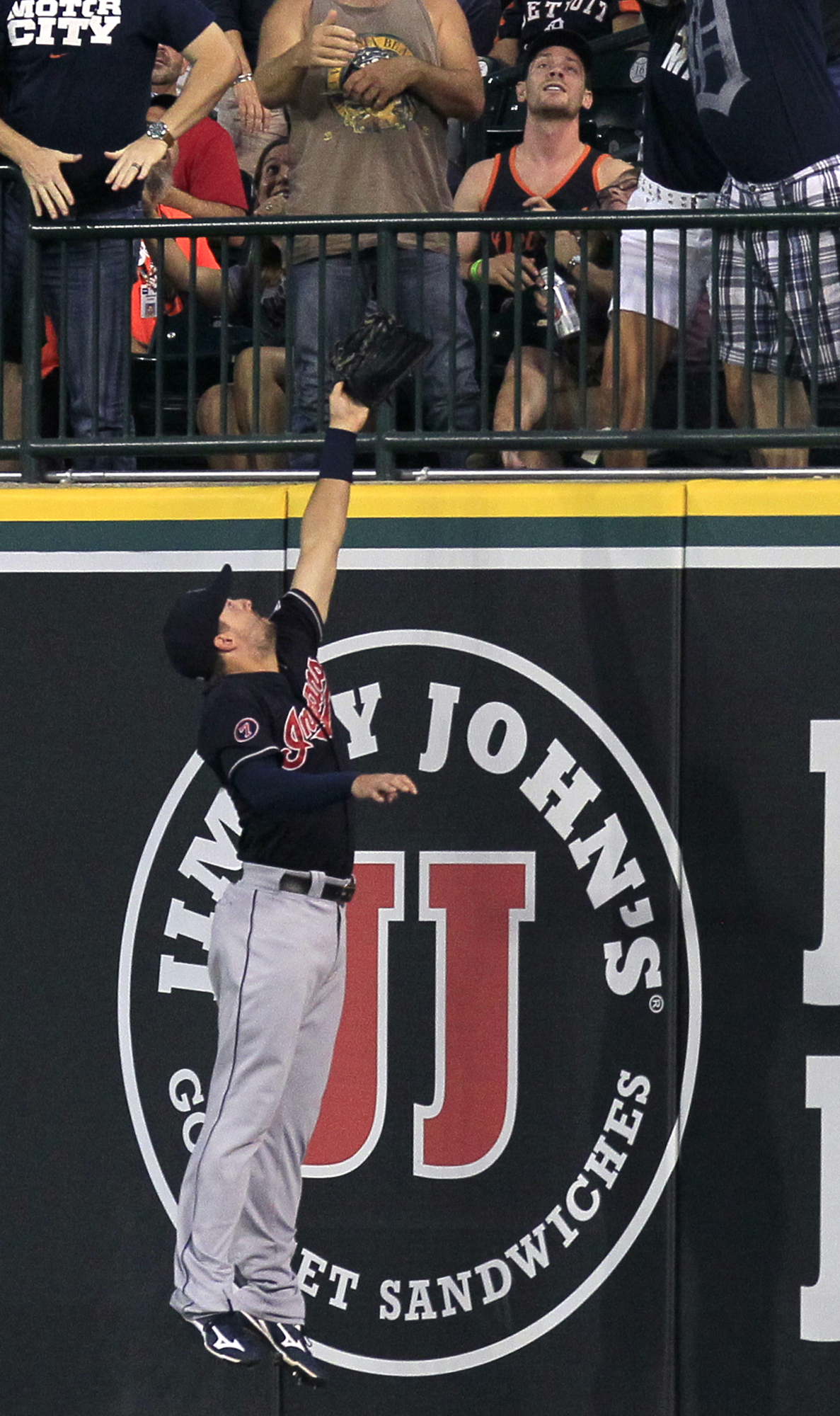 Cleveland Indians right fielder Lonnie Chisenhall leaps against the right field wall while trying to catch a home run hit by Detroit Tigers' J.D. Martinez during the third inning of a baseball game Saturday, Sept. 5, 2015, in Detroit. (AP Photo/Duane Burl