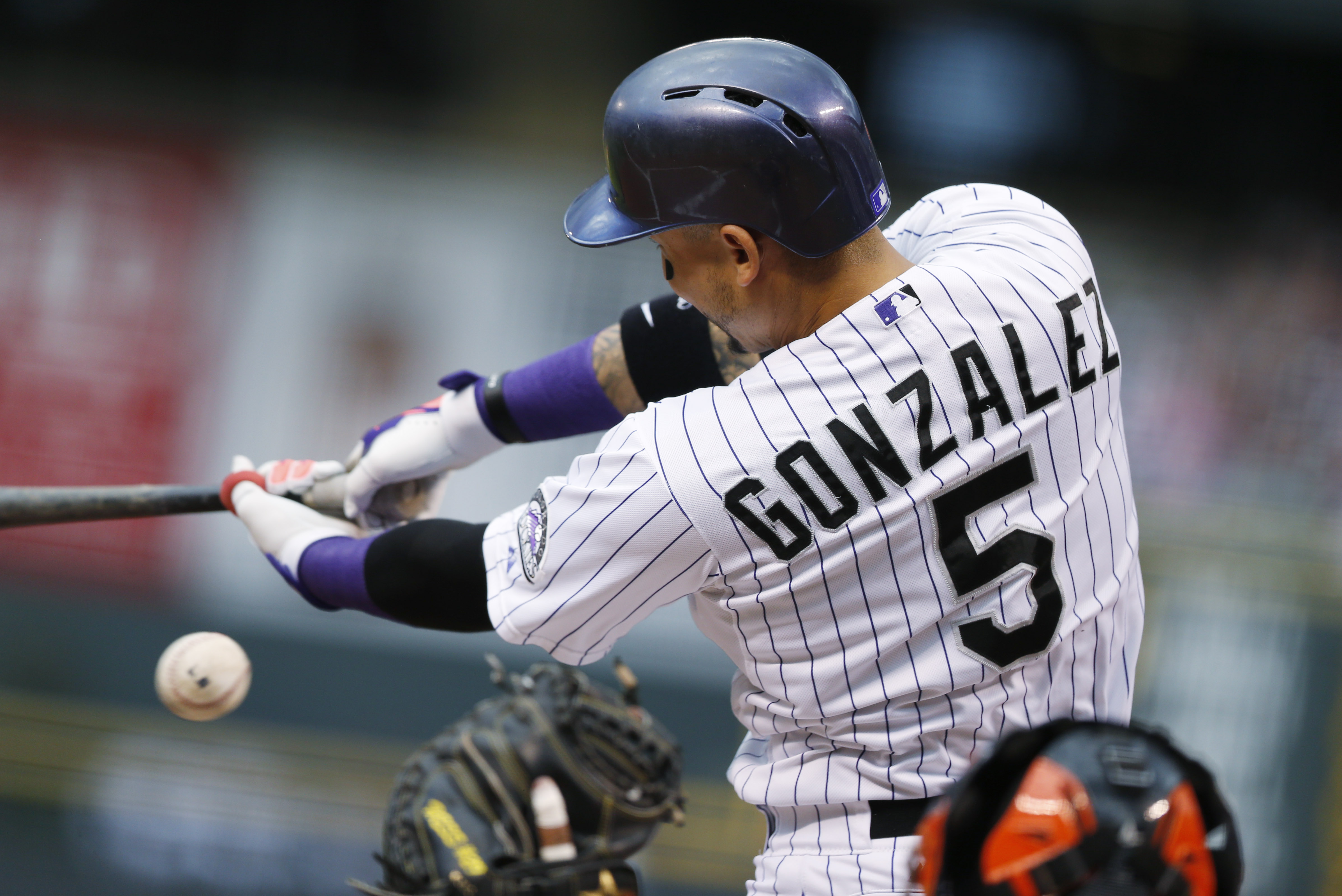 Colorado Rockies' Carlos Gonzalez, back, swings and misses a pitch as San Francisco Giants catcher Hector Sanchez fields the throw from Giants starting pitcher Jake Peavy in the first inning of a baseball game Saturday, Sept. 5, 2015, in Denver. (AP Photo