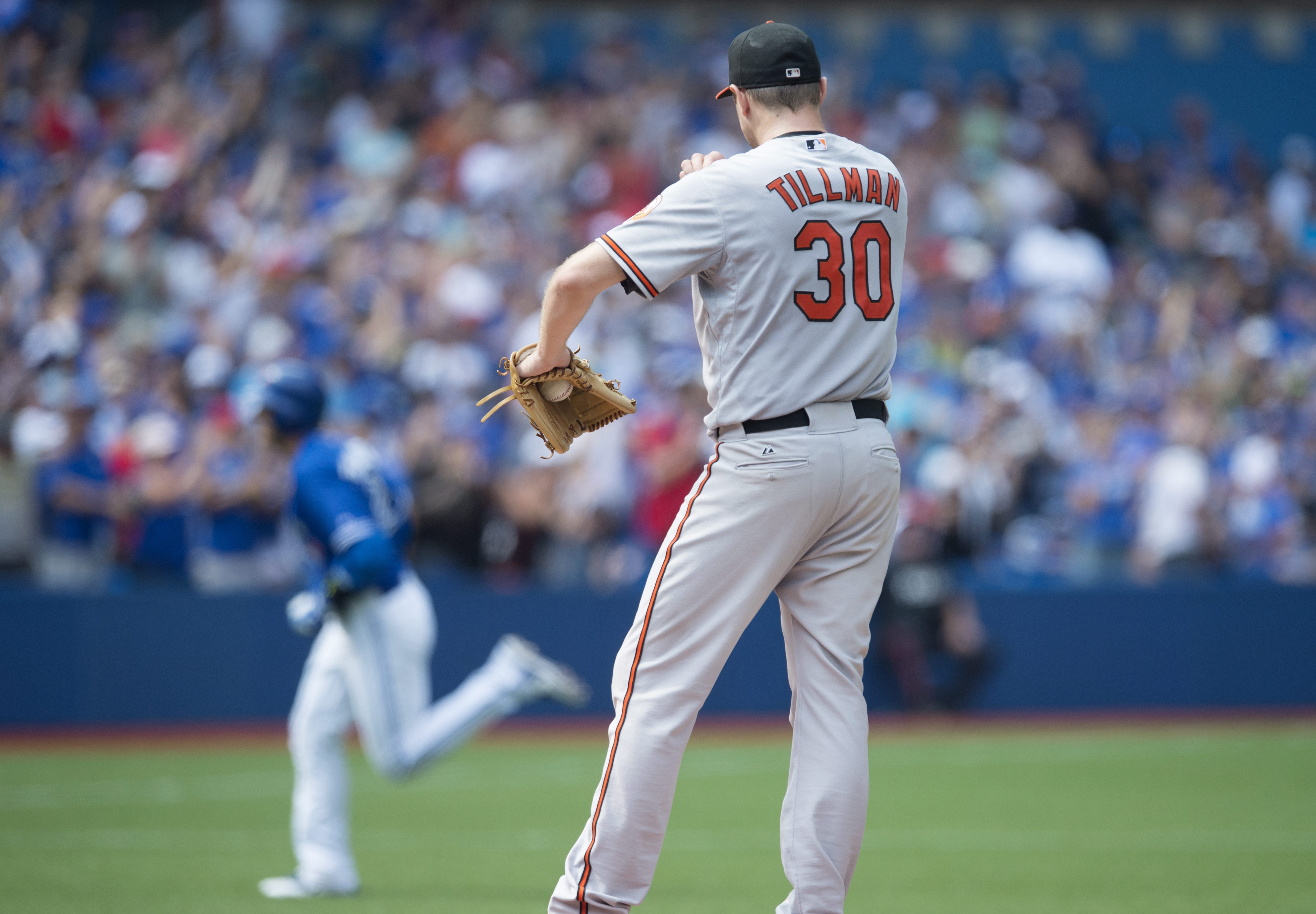 Baltimore Orioles starting pitcher Chris Tillman, right, stands on the mound as Toronto Blue Jays' Troy Tulowitzki rounds the bases following a two-run home run during third-inning baseball game action in Toronto, Sunday, Sept. 6, 2015. (Darren Calabrese/