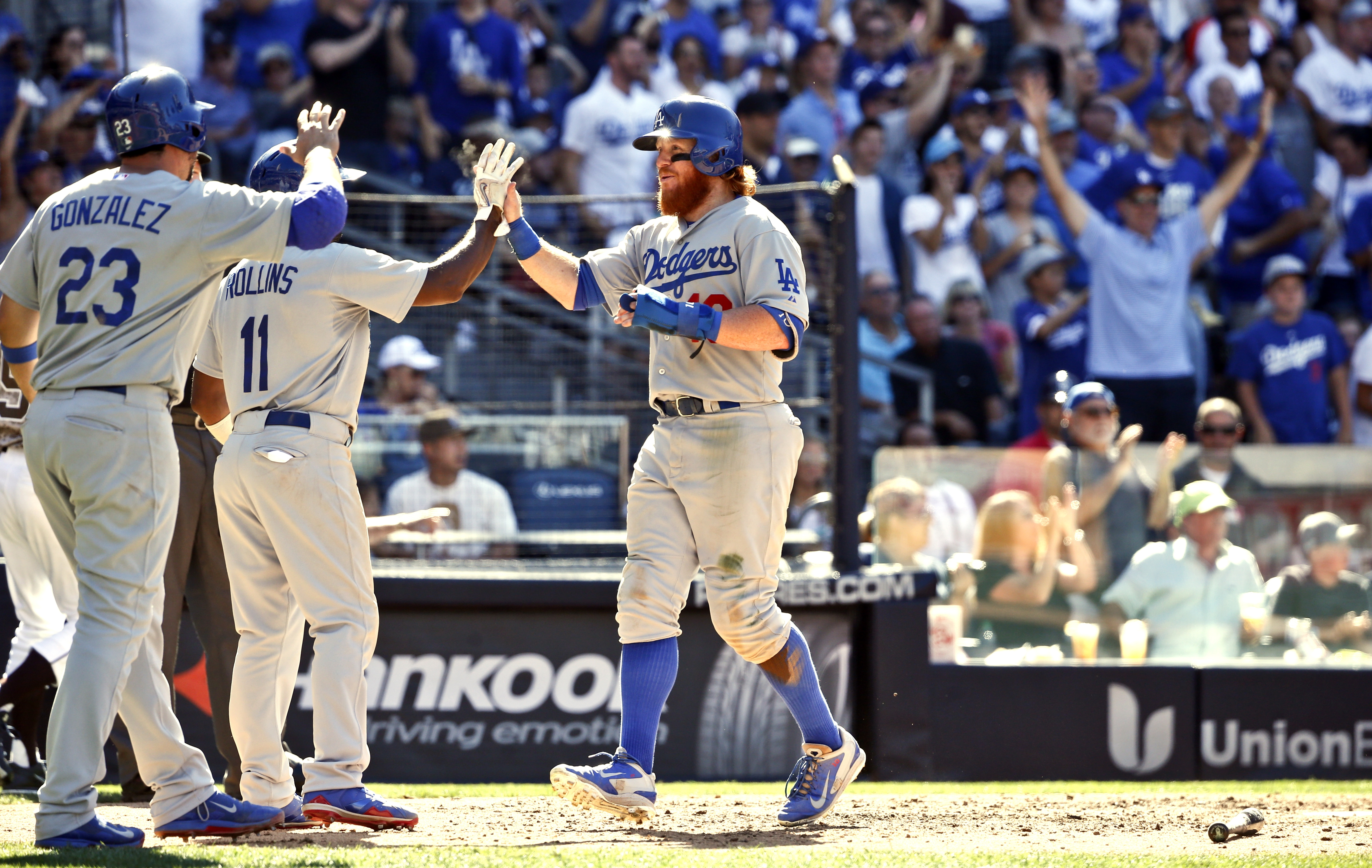 Los Angeles Dodgers' Justin Turner, right, is met by teammates Jimmy Rollins and Adrian Gonzalez after the three scored when San Diego Padres relief pitcher Nick Vincent made a wild throw to first base in the seventh inning of a baseball game Sunday, Sept