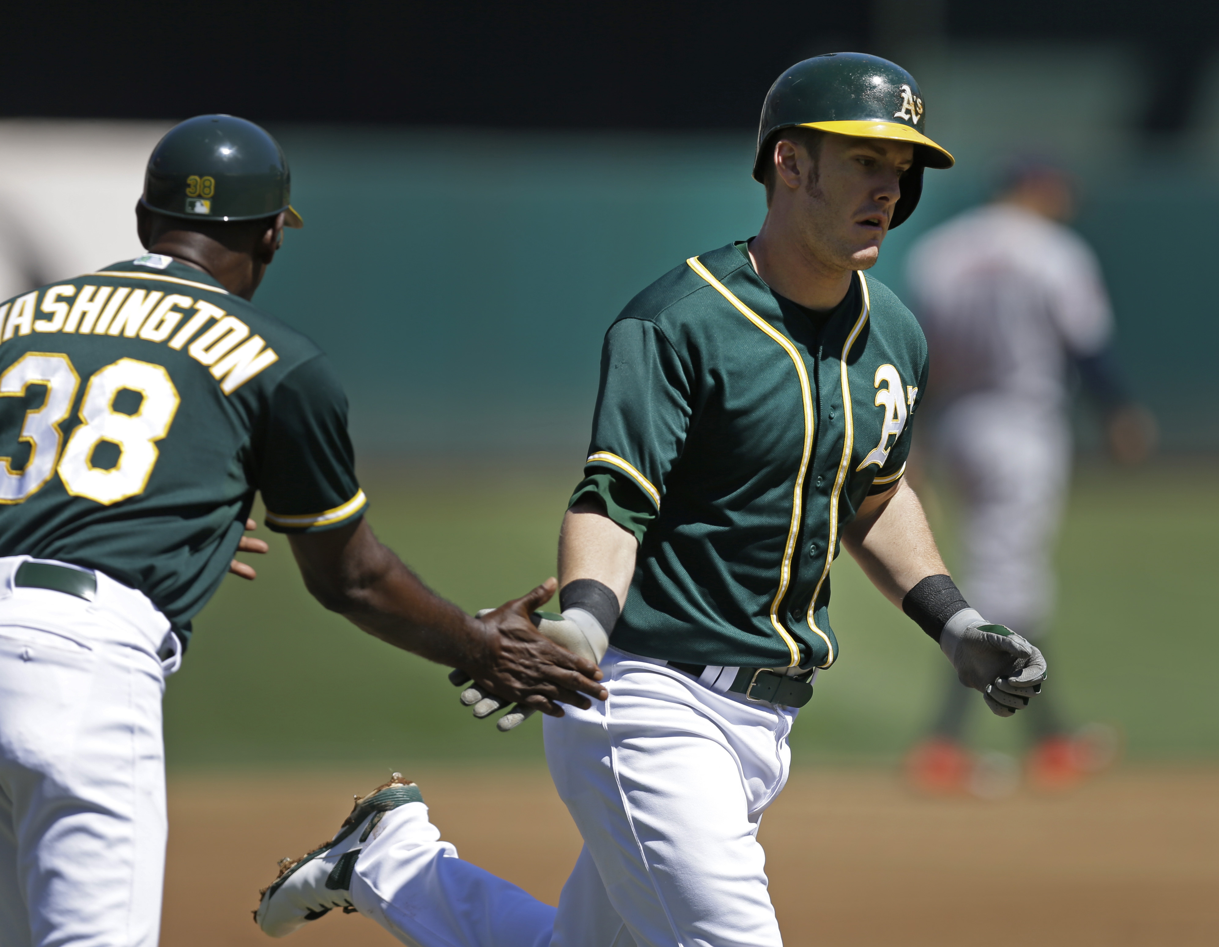 Oakland Athletics' Mark Canha, right, is congratulated by third base coach Ron Washington (38) after hitting a home run off Houston Astros pitcher Mike Fiers in the first inning of a baseball game Monday, Sept. 7, 2015, in Oakland, Calif. (AP Photo/Ben Ma