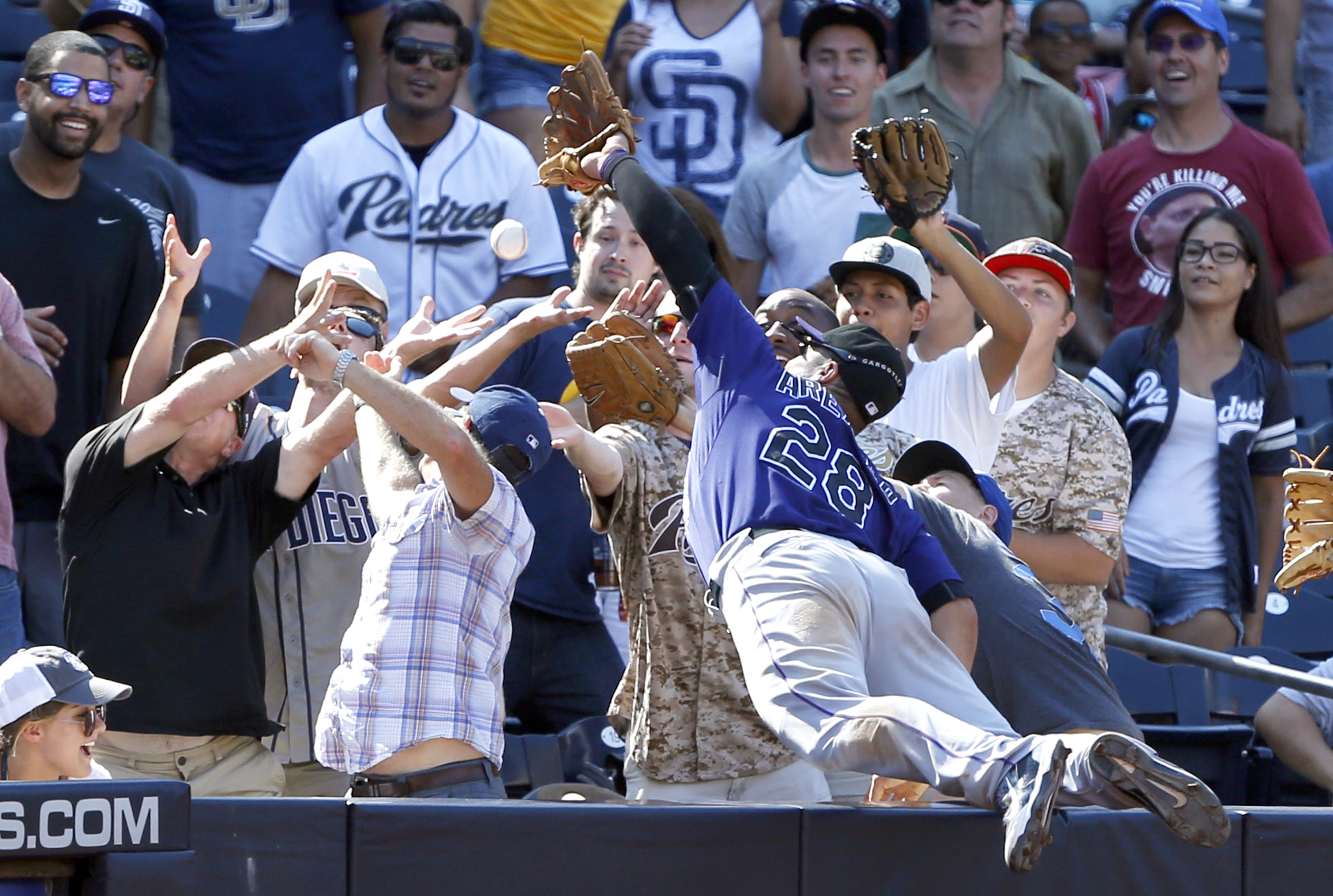 Colorado Rockies third baseman Nolan Arenado (28) leaps into the stands but cannot reach a foul ball hit by San Diego Padres' Wil Myers during the sixth inning of a baseball game in San Diego, Calif., Monday, Sept. 7, 2015. Myers would later strike out, w