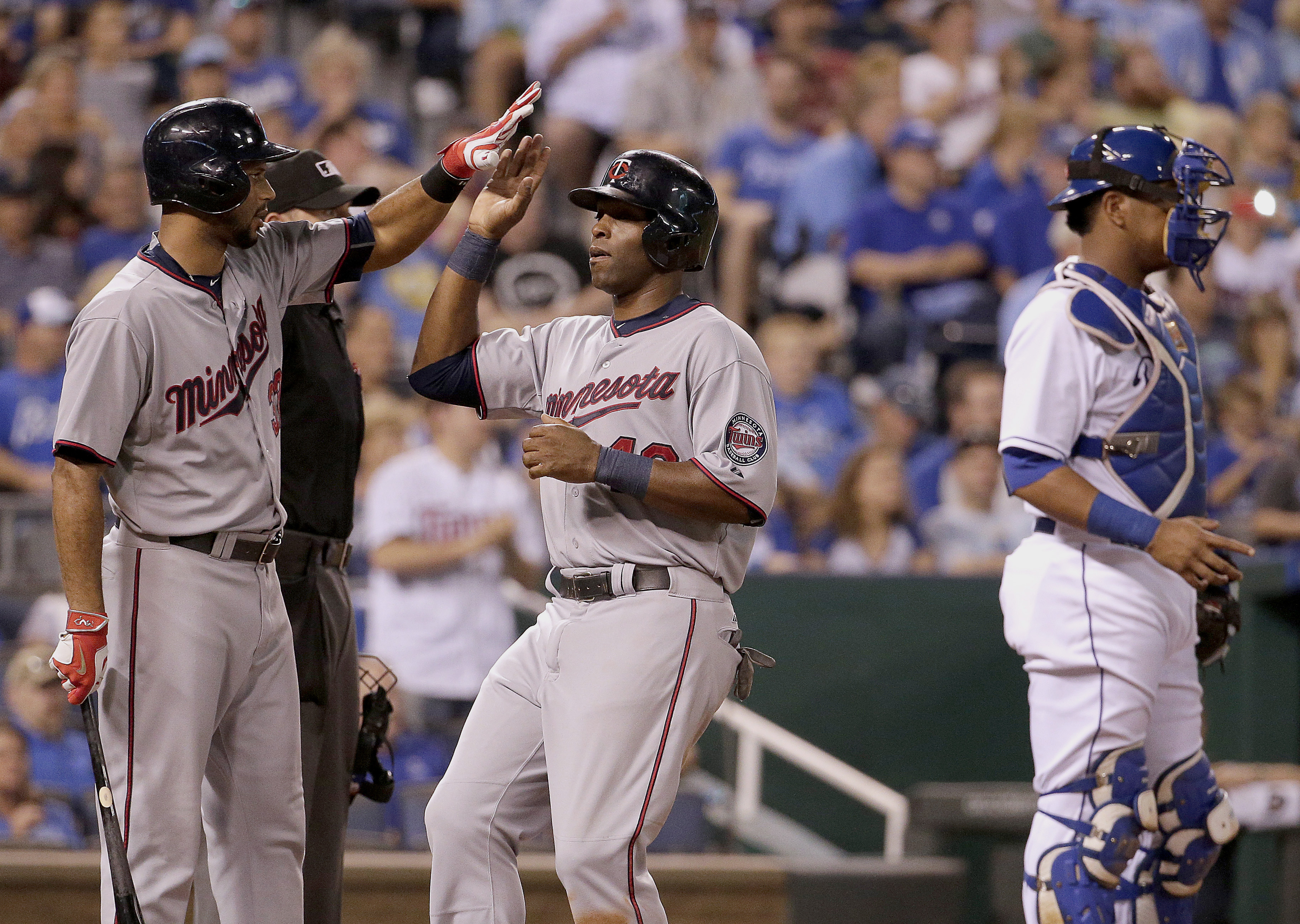 Minnesota Twins' Torii Hunter, center, celebrates with Aaron Hicks after Hunter scored on a single by Eduardo Escobar during the sixth inning of a baseball game against the Kansas City Royals, Monday, Sept. 7, 2015, in Kansas City, Mo. (AP Photo/Charlie R