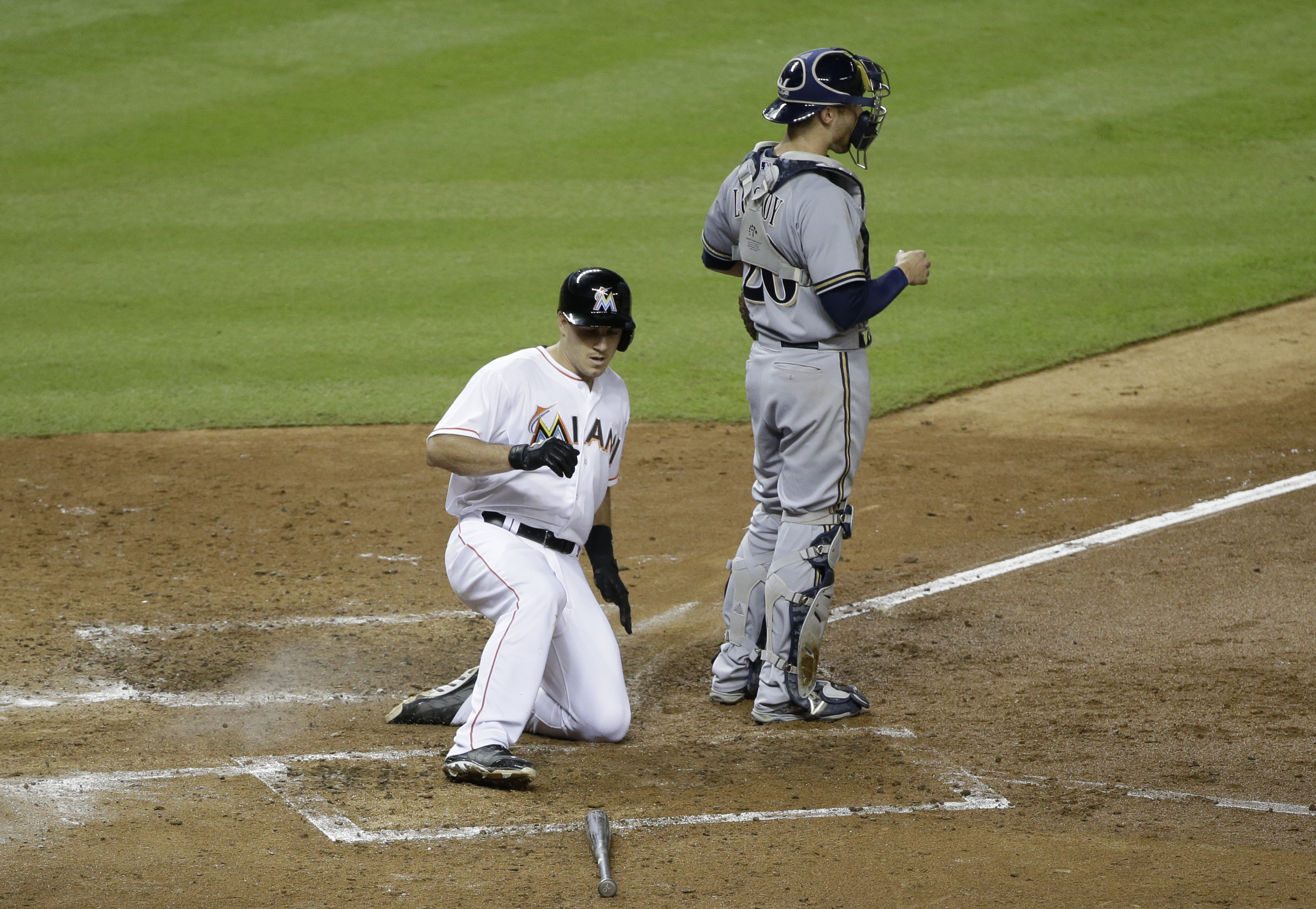 Miami Marlins' J.T. Realmuto slides into home plate as Milwaukee Brewers catcher Jonathan Lucroy waits for the throw after Realmuto hit an inside-the-park home run during the fourth inning of a baseball game against the Milwaukee Brewers, Tuesday, Sept. 8