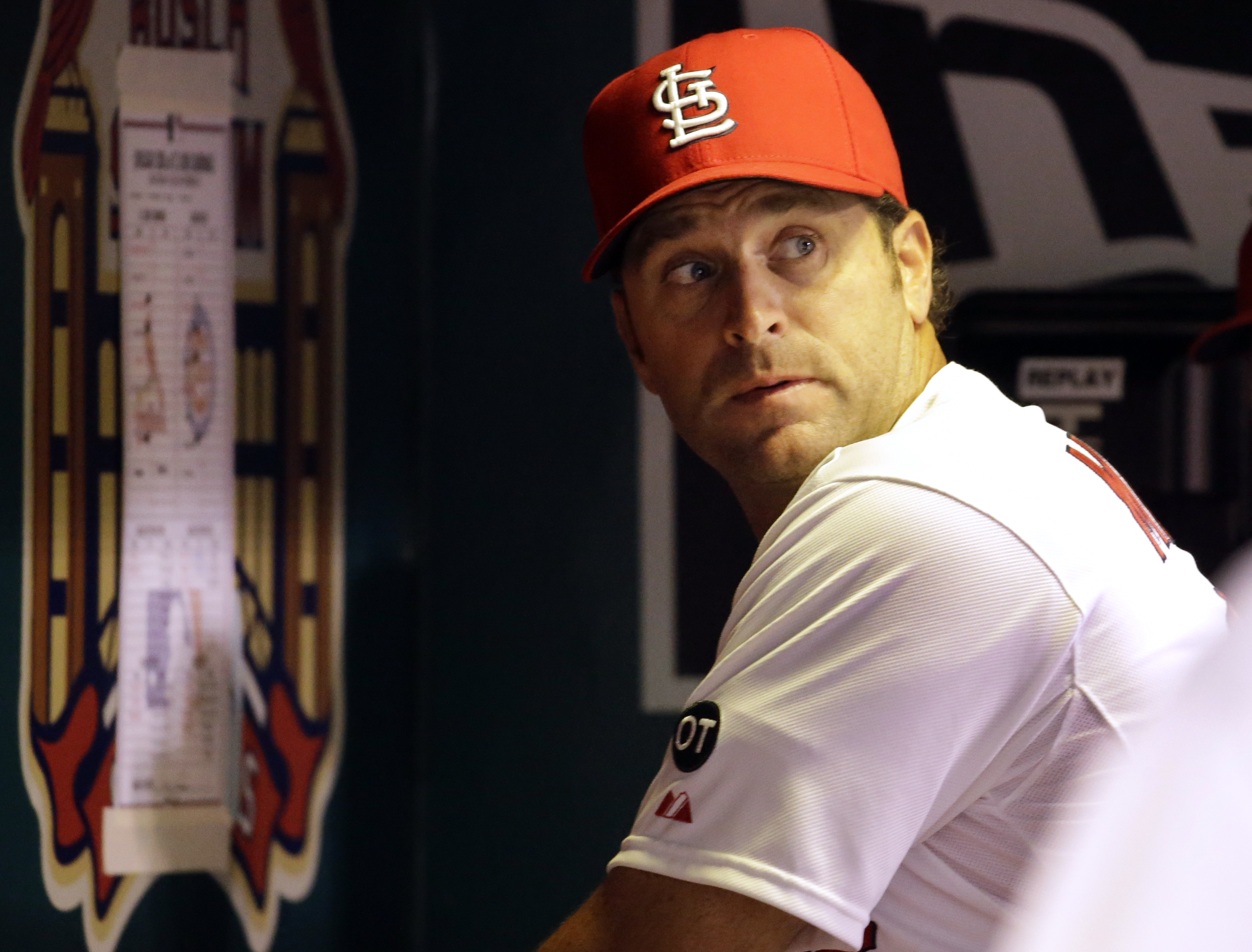 St. Louis Cardinals manager Mike Matheny looks over his shoulder toward the field after looking at a line-up card taped to the dugout wall during the fourth inning of the Cardinals' baseball game against the Chicago Cubs on Tuesday, Sept. 8, 2015, in St.