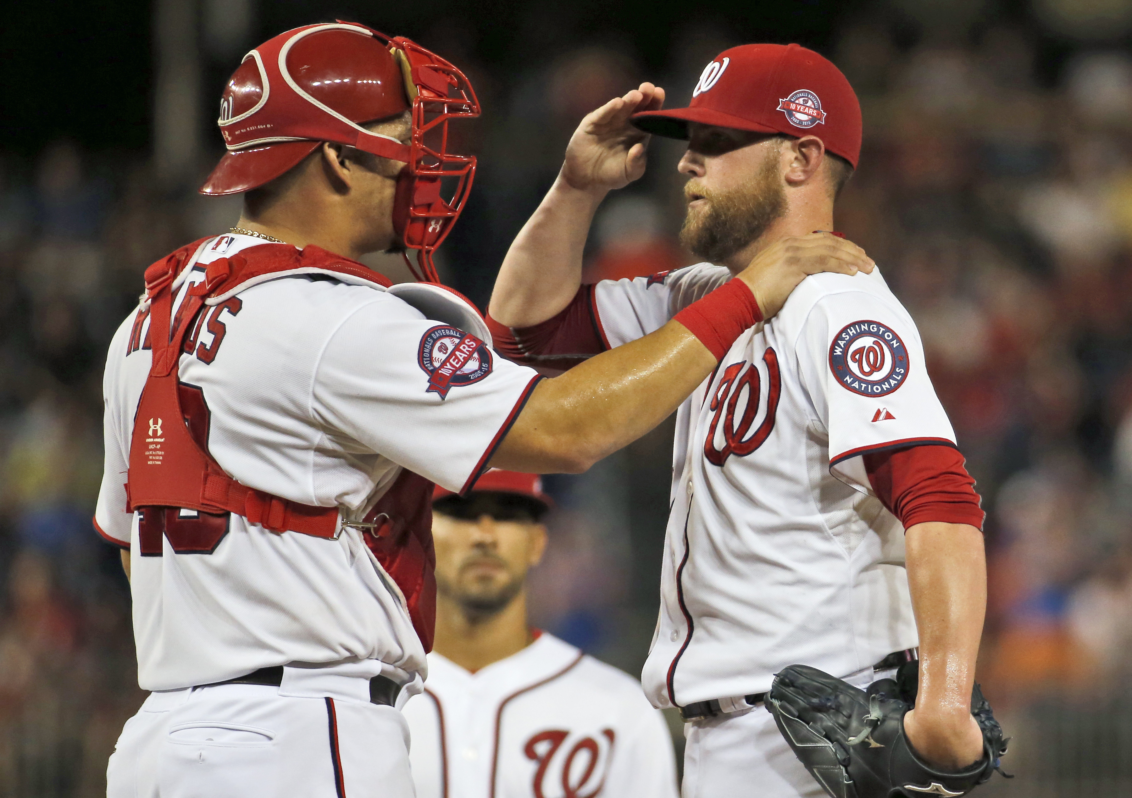 Washington Nationals catcher Wilson Ramos (40) talks with relief pitcher Drew Storen, right, with shortstop Ian Desmond behind, after Storen walked in a run to tie the baseball game against the New York Mets during the seventh inning at Nationals Park, Tu