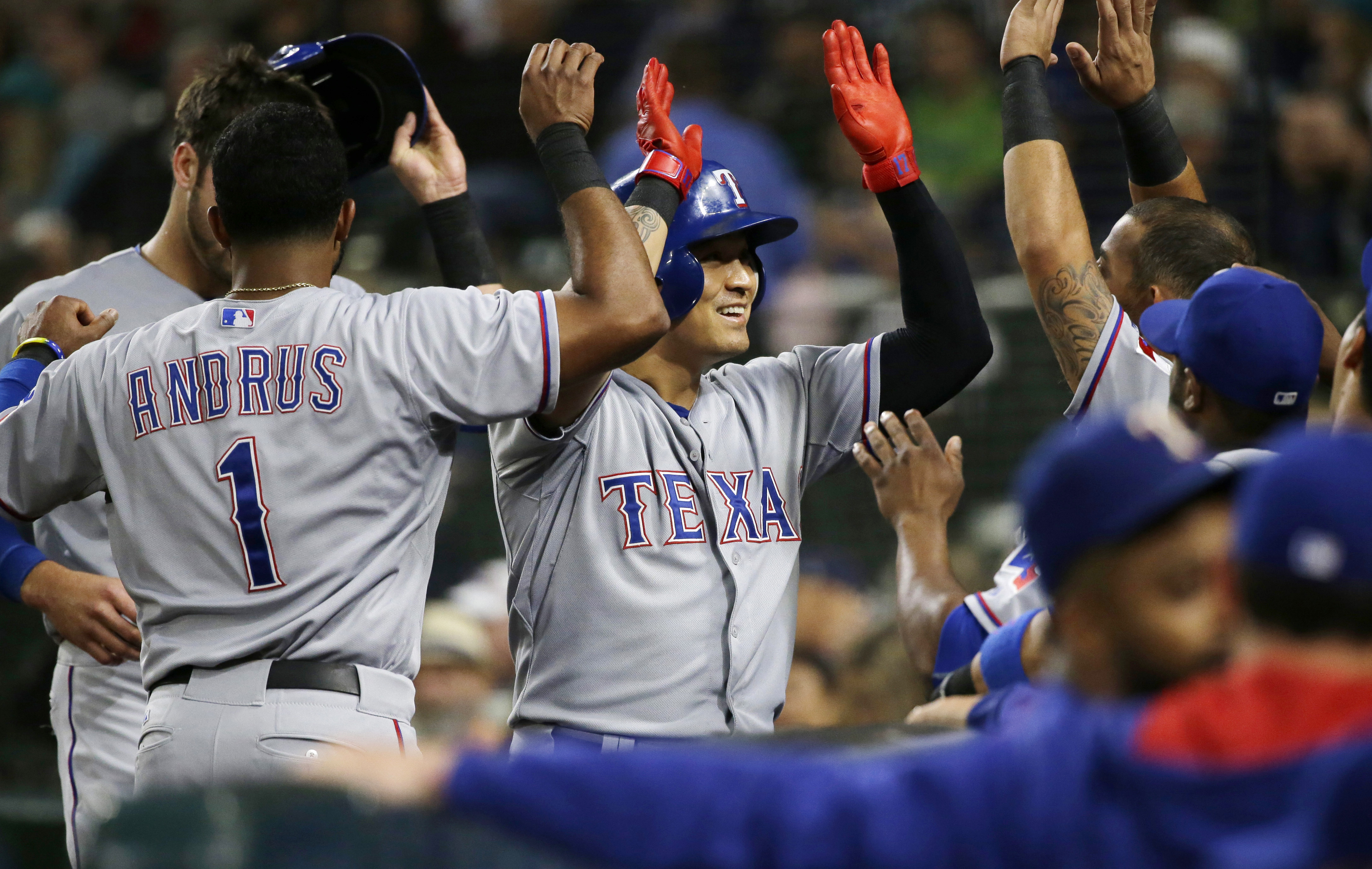 Texas Rangers' Shin-Soo Choo, center, is greeted at the dugout after he hit a three-run home run during the third inning of a baseball game against the Seattle Mariners, Tuesday, Sept. 8, 2015, in Seattle. (AP Photo/Ted S. Warren)