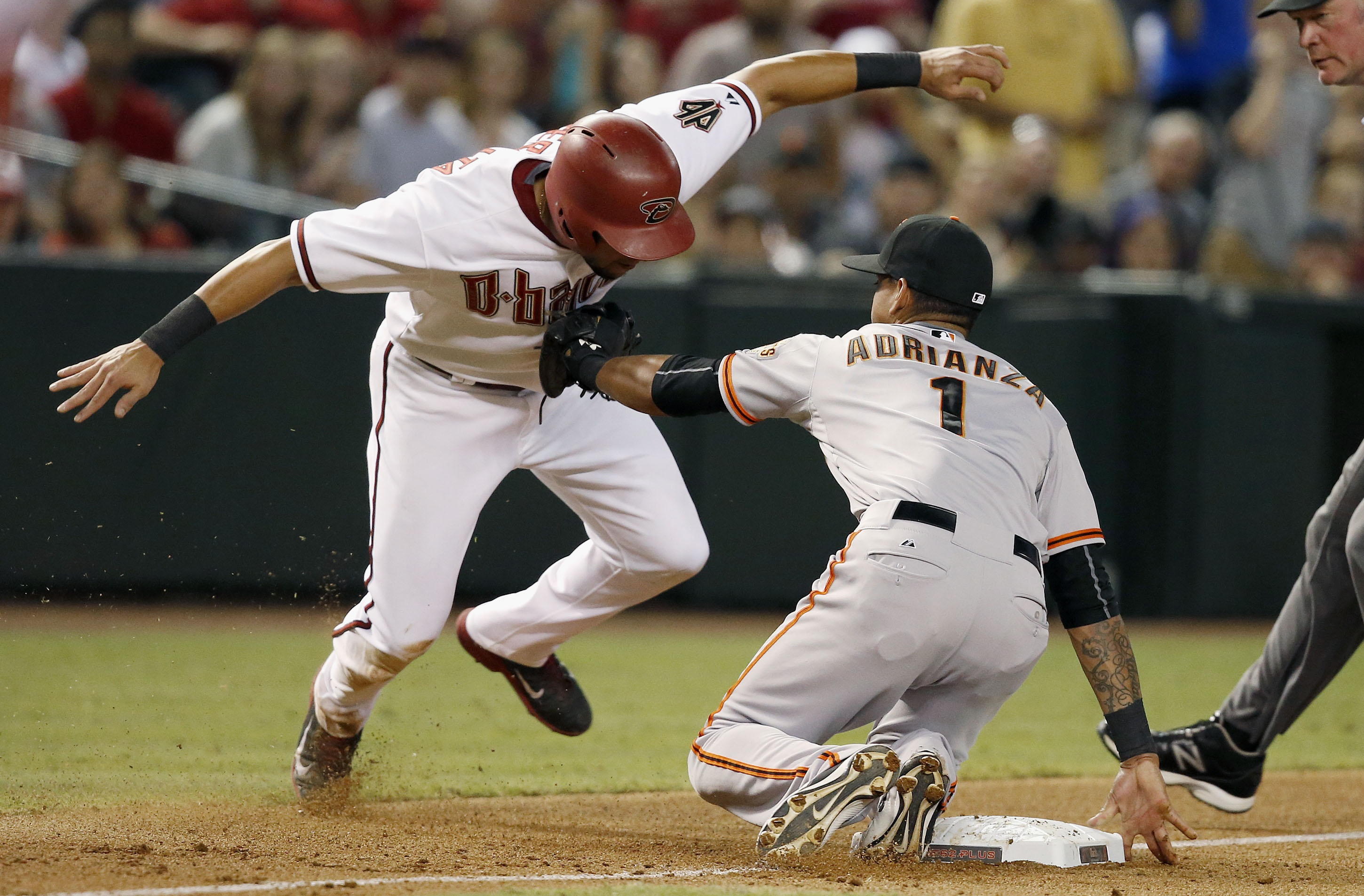 San Francisco Giants' Ehire Adrianza (1) tags Arizona Diamondbacks' David Peralta, left, out at third base during the fourth inning of a baseball game Tuesday, Sept. 8, 2015, in Phoenix. (AP Photo/Ross D. Franklin)