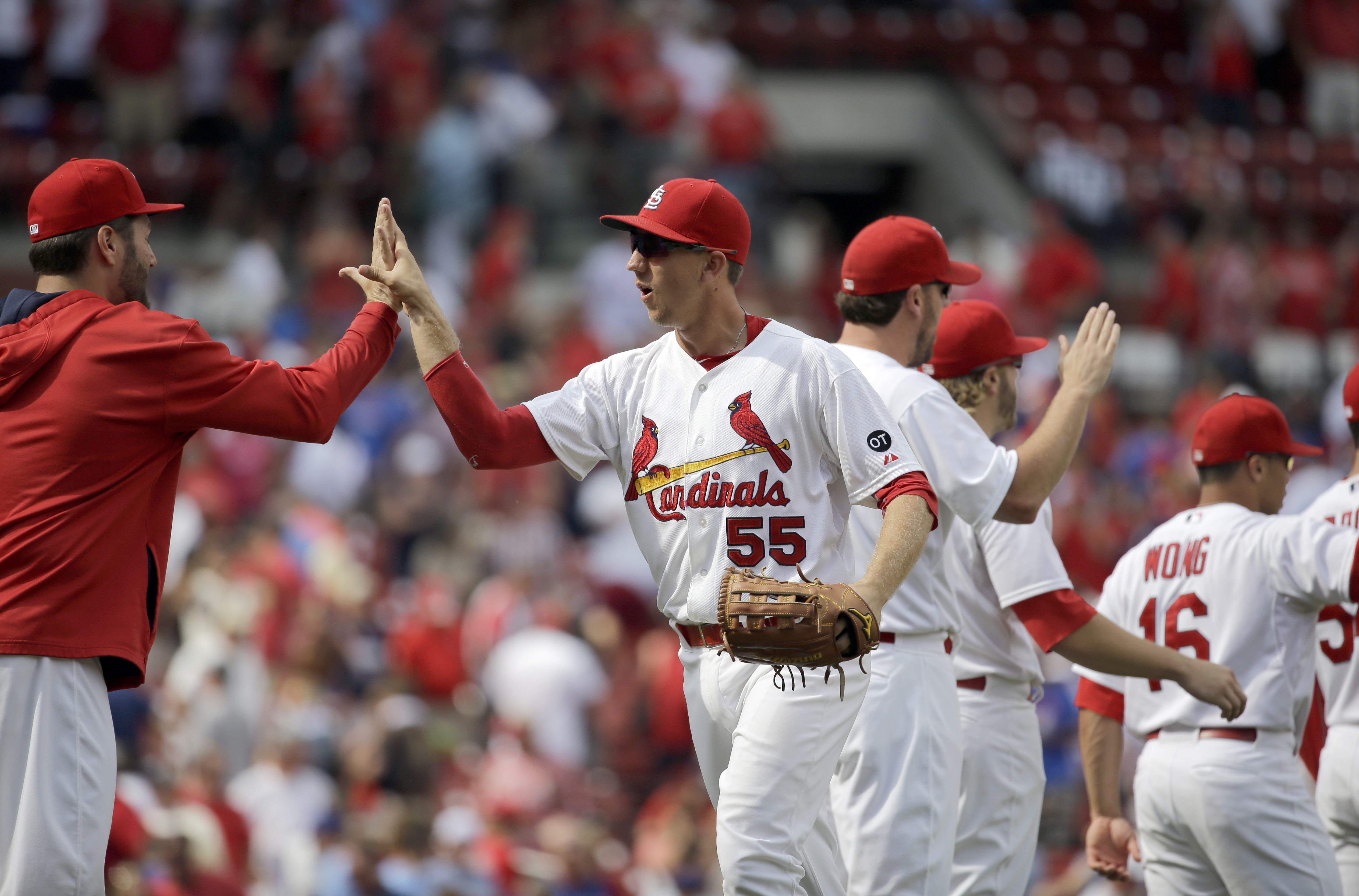 St. Louis Cardinals' Stephen Piscotty (55) gets a high-five from teammate Lance Lynn, left, as they celebrate with teammates following their 4-3 victory over the Chicago Cubs in a baseball game, Wednesday, Sept. 9, 2015, in St. Louis. (AP Photo/Jeff Rober
