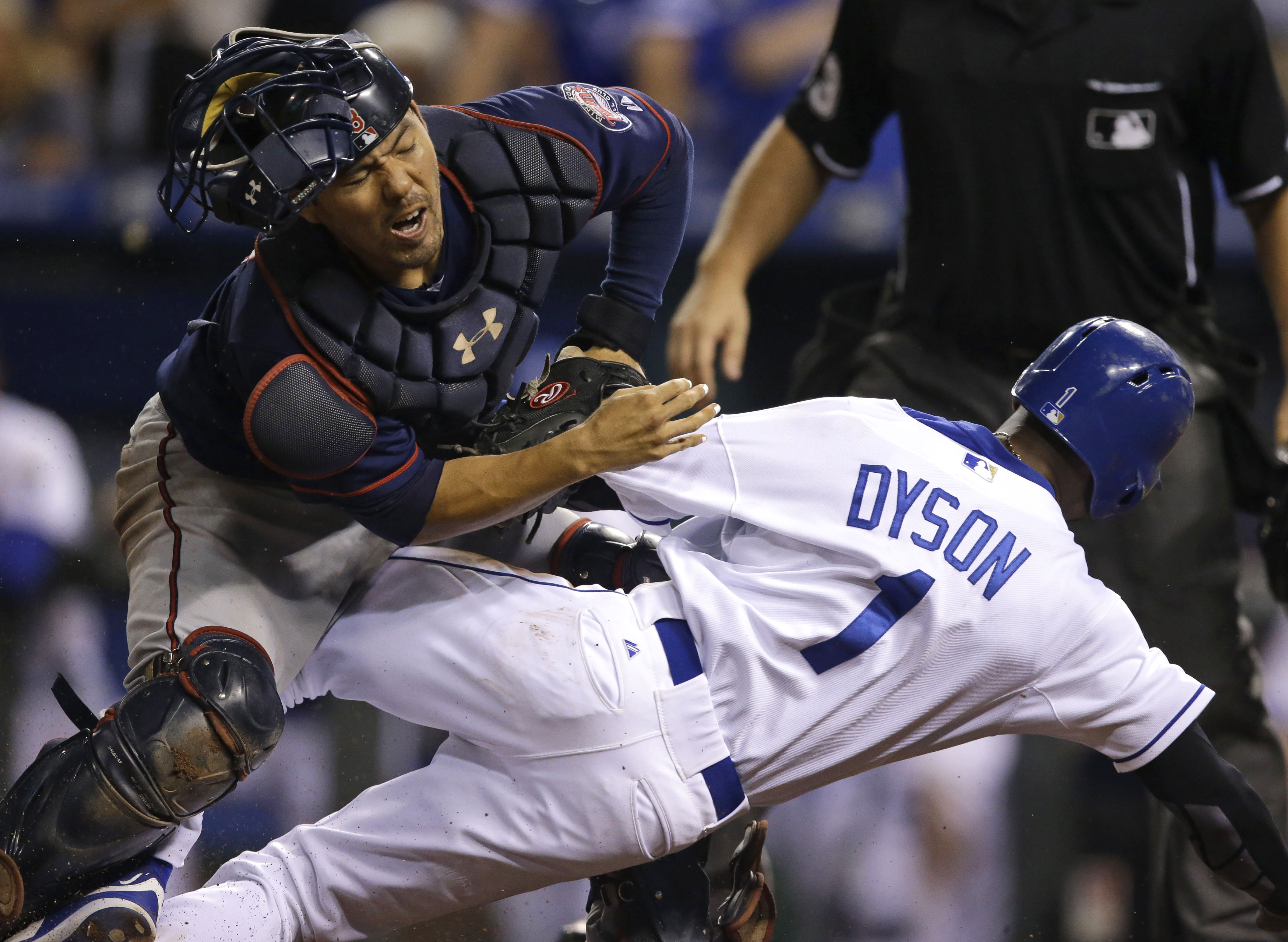 Minnesota Twins catcher Kurt Suzuki, left, tags out Kansas City Royals' Jarrod Dyson (1) during the 10th inning of a baseball game at Kauffman Stadium in Kansas City, Mo., Wednesday, Sept. 9, 2015. Suzuki was injured on the play. (AP Photo/Orlin Wagner)
