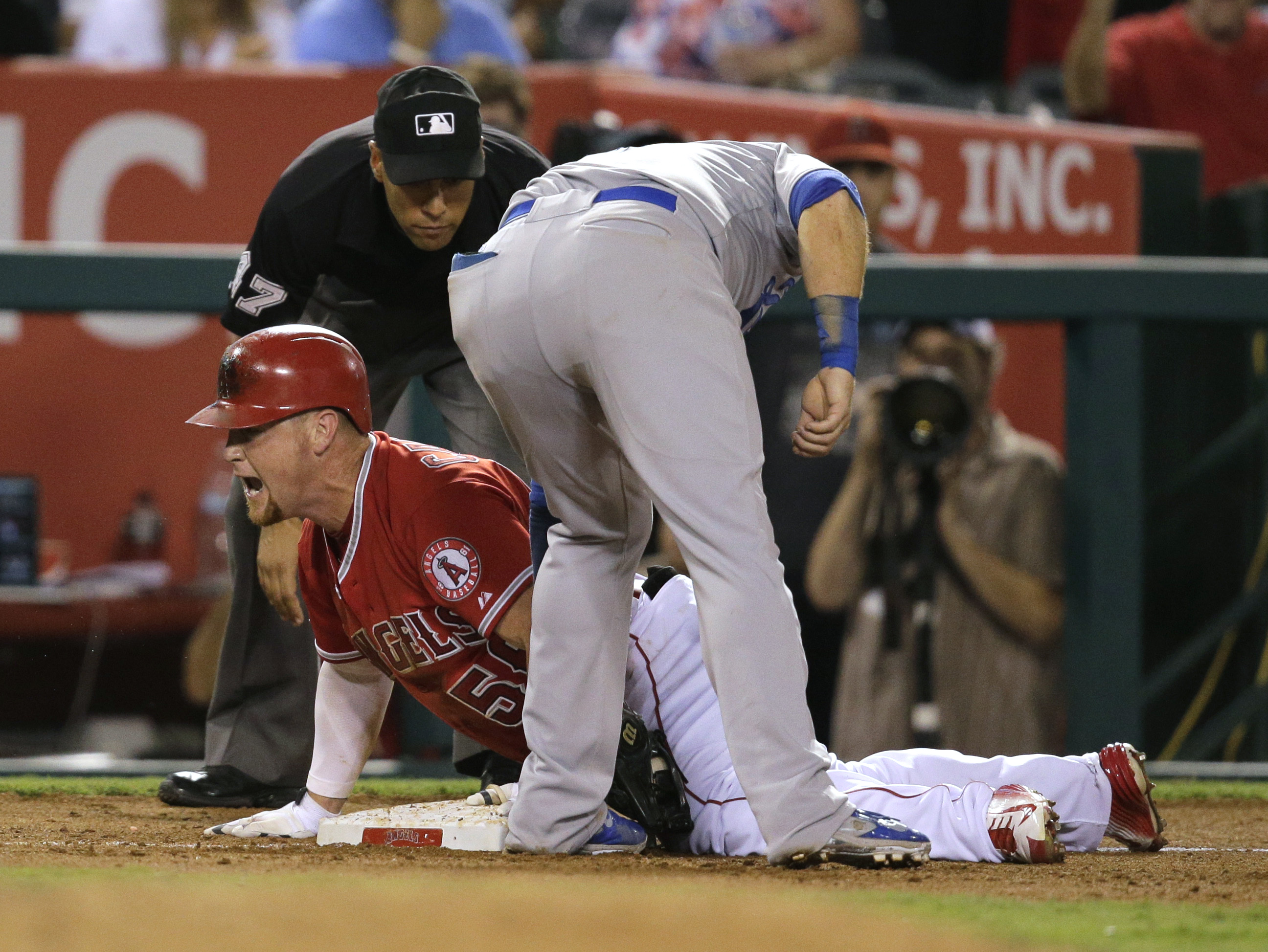 Los Angeles Angels' Kole Calhoun, left, celebrates his triple as Los Angeles Dodgers third baseman Justin Turner applies a late tag during the eighth inning of a baseball game, Wednesday, Sept. 9, 2015, in Anaheim, Calif. (AP Photo/Jae C. Hong)