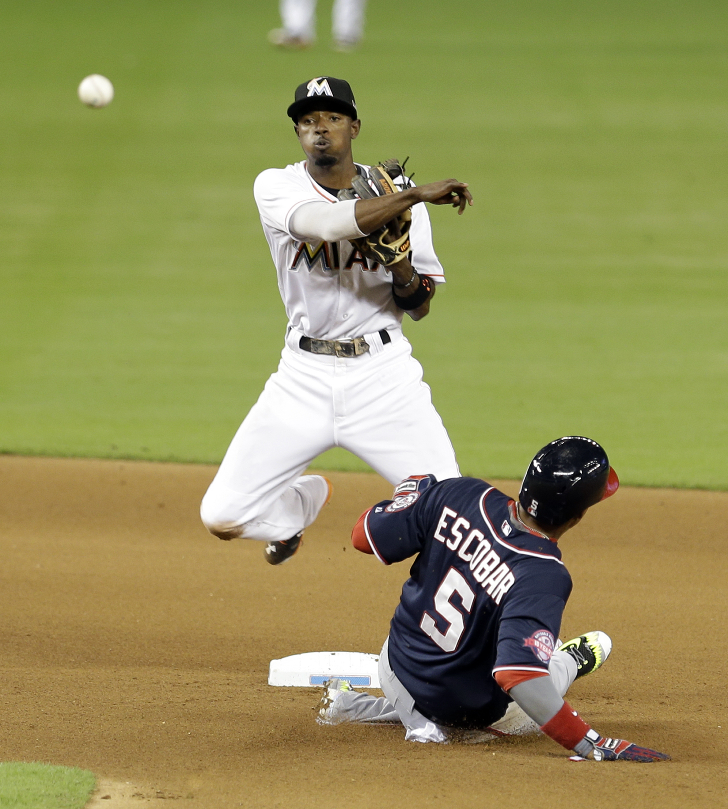 Washington Nationals' Yunel Escobar (5) is forced out at second base as Miami Marlins second baseman Dee Gordon (9) throws to first base to complete the double play in the fourth inning of a baseball game Friday, Sept. 11, 2015, in Miami. Ian Desmond was