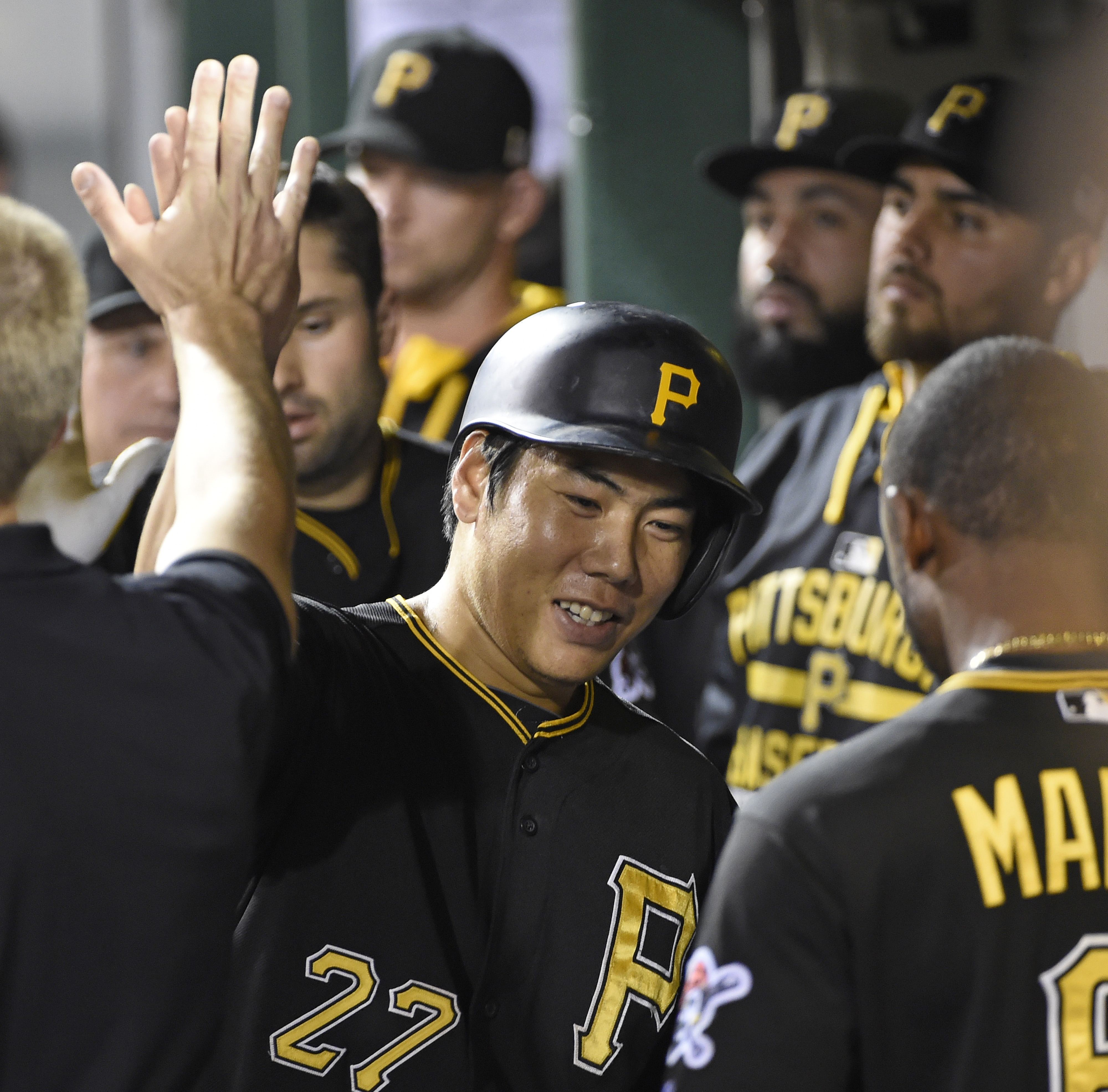Pittsburgh Pirates' Jung Ho Kang (27) is congratulated in the dugout after scoring a run against the Milwaukee Brewers in the seventh inning of a baseball game, Friday, Sept. 11, 2015, in Pittsburgh. (AP Photo/Fred Vuich)
