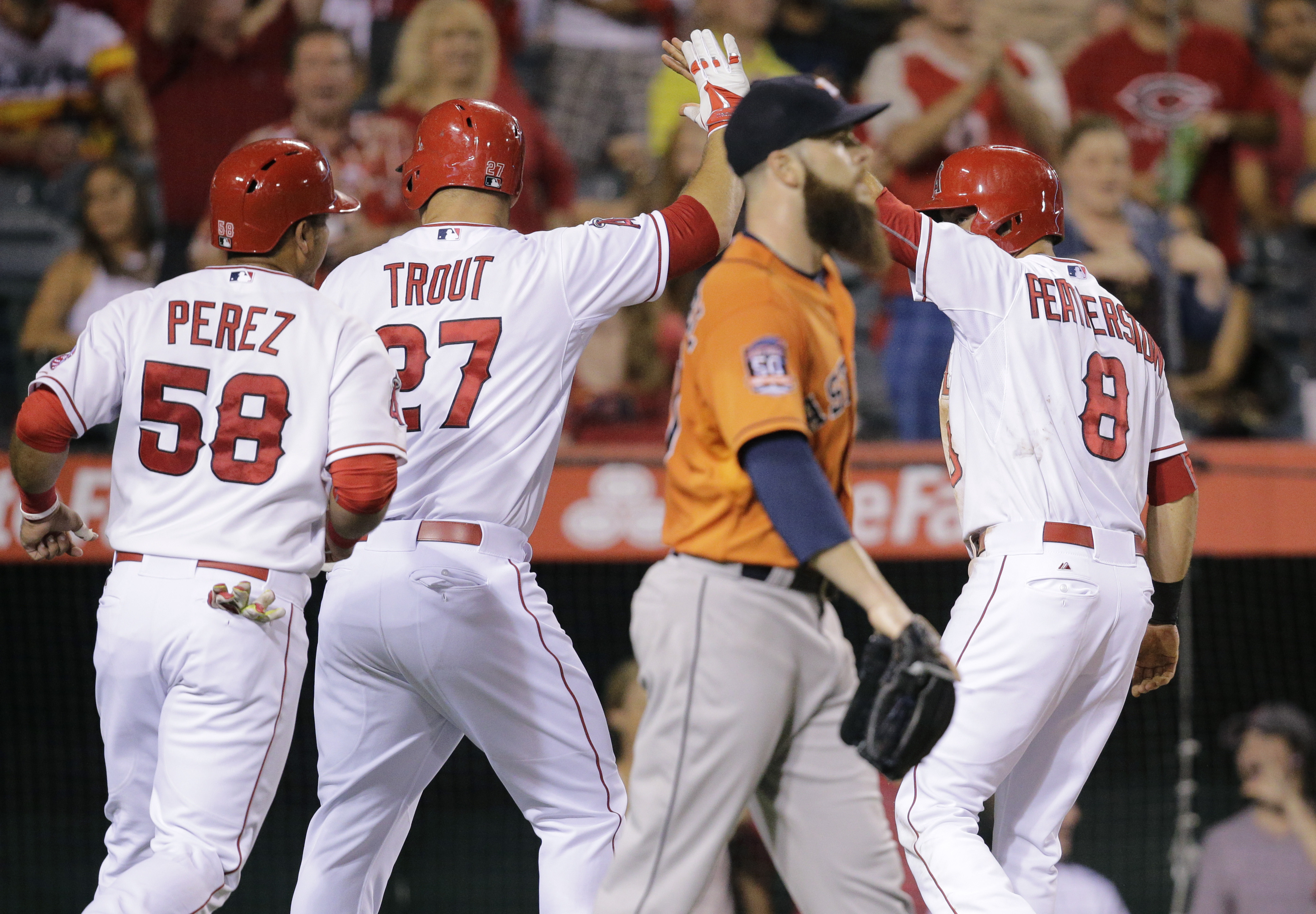 Los Angeles Angels' Taylor Featherston (8), Carlos Perez (58) and Mike Trout (27) celebrate after Featherston and Perez scored on a single by Los Angeles Angels' Kole Calhoun as Houston Astros starting pitcher Dallas Keuchel, foreground, walks toward the