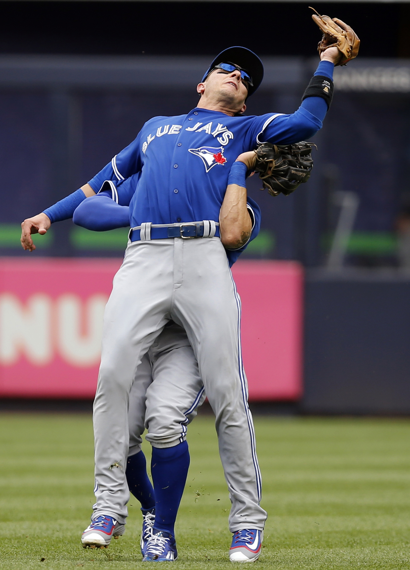 Toronto Blue Jays shortstop Troy Tulowitzki, foreground, collides with Blue Jays center fielder Kevin Pillar fielding a fly ball in a baseball game at Yankee Stadium in New York, Saturday, Sept. 12, 2015.  (AP Photo/Kathy Willens)