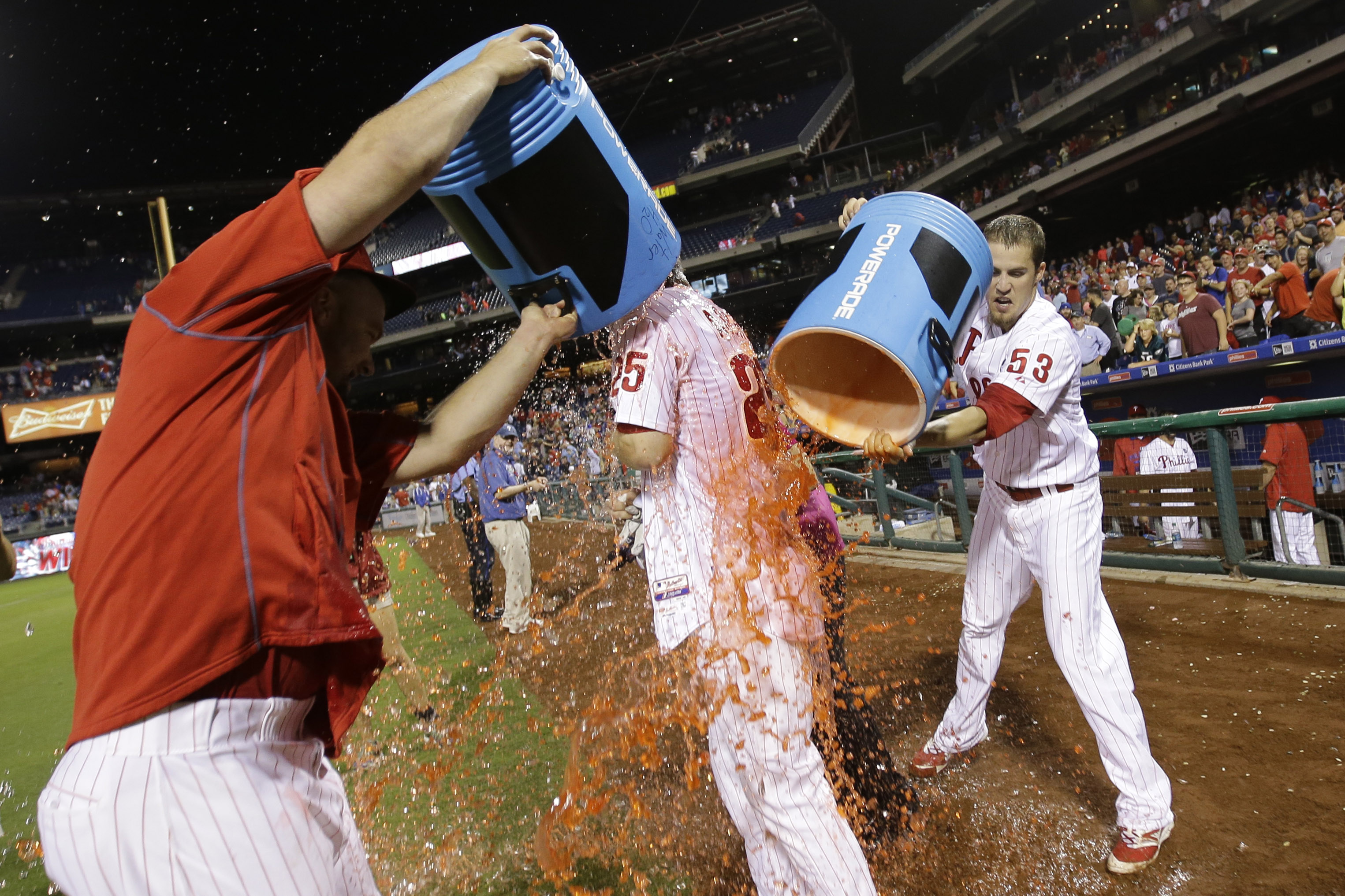 CORRECTS SPELLING OF NAME TO ASCHE NOT ASHE IN SECOND REFERENCE Philadelphia Phillies' Cody Asche, center, is doused by Ken Giles, right, and Cameron Rupp  after Asche hit a walk-off two-run home run off Chicago Cubs relief pitcher Hector Rondon during th