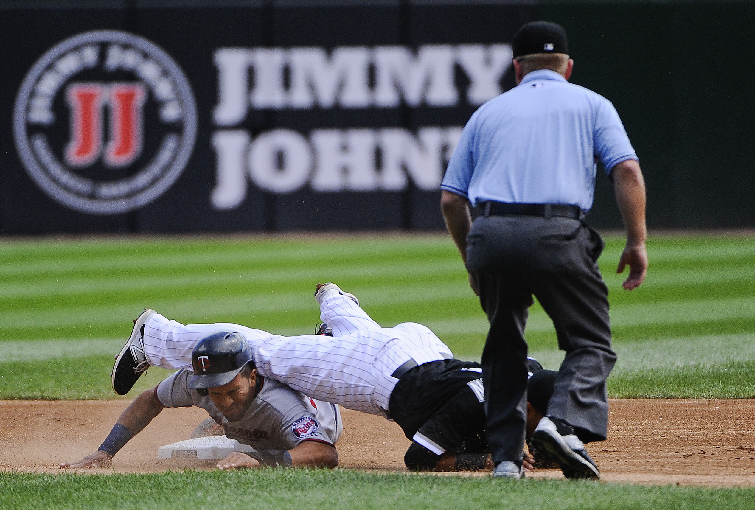 Minnesota Twins Eddie Rosario, left,  is caught settling second base by Chicago White Sox second baseman Micah Johnson in the first inning of a baseball game on Sunday, Sept. 13, 2015, in Chicago. (AP Photo/Matt Marton)