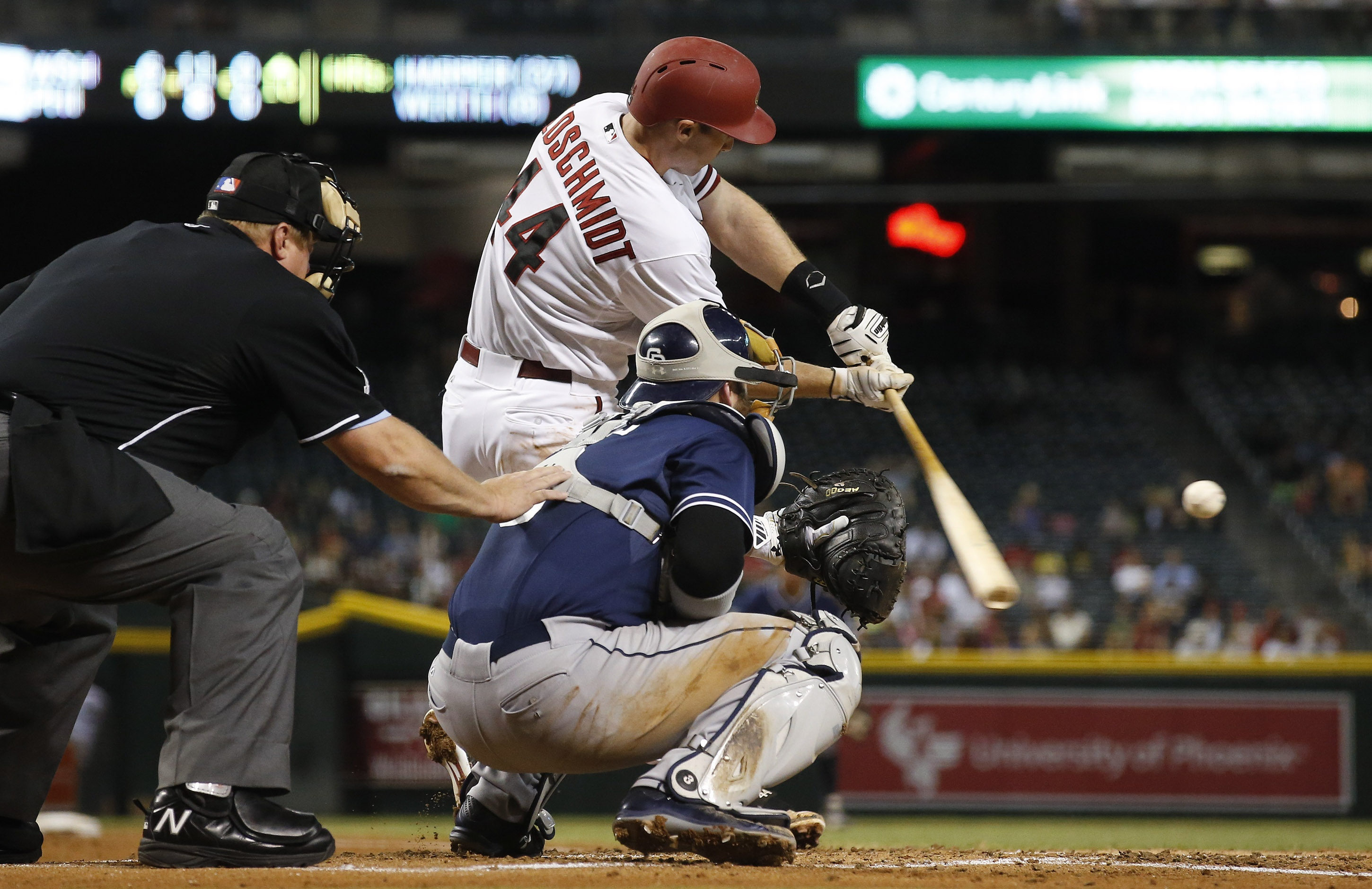 Arizona Diamondbacks' Paul Goldschmidt (44) connects for a run-scoring double as San Diego Padres catcher Derek Norris and umpire Bruce Dreckman, left, watches during the first inning of a baseball game Monday, Sept. 14, 2015, in Phoenix. (AP Photo/Ross D