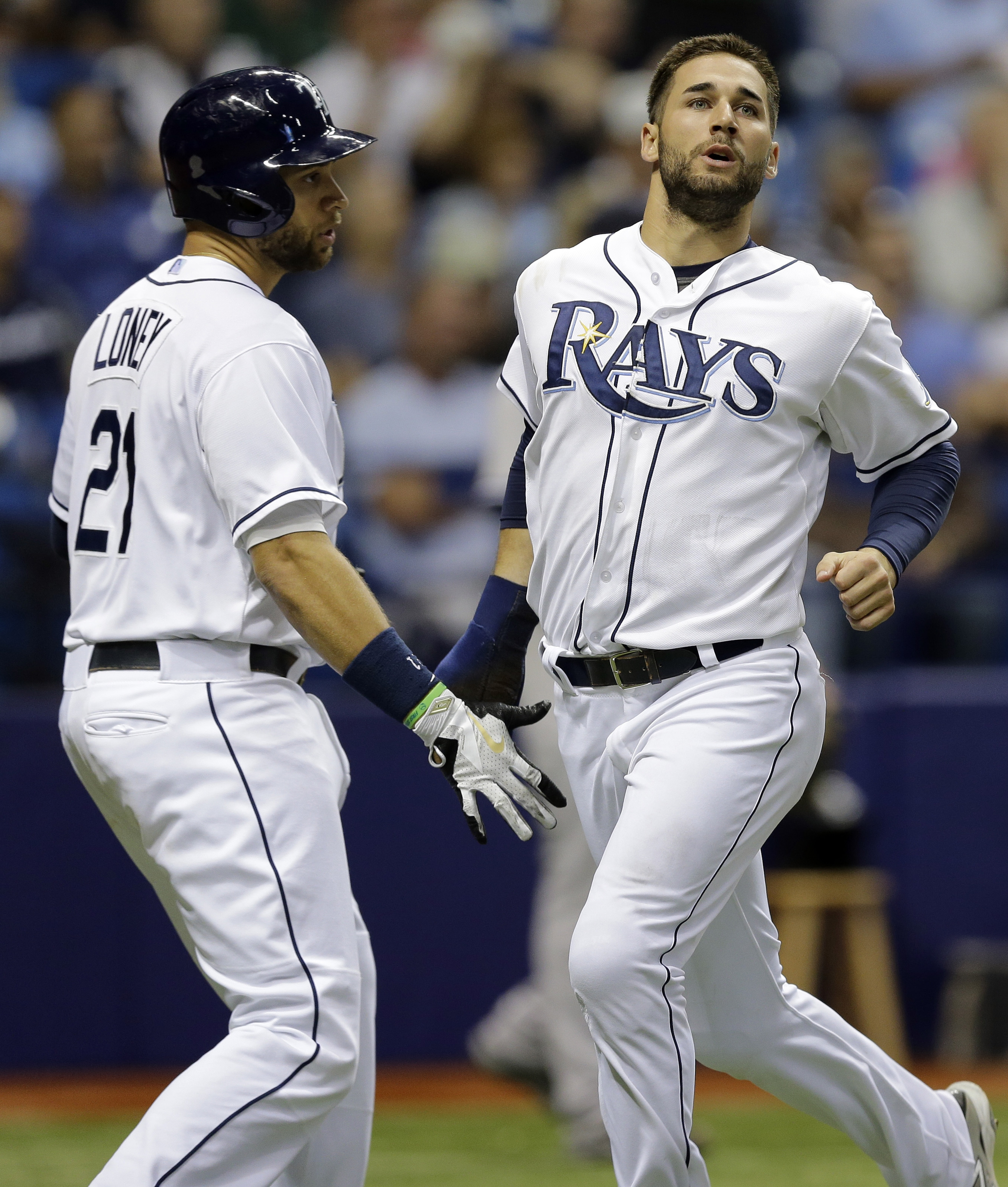 Tampa Bay Rays' Kevin Kiermaier, right, celebrates with James Loney after scoring on a single by J.P. Arencibia off New York Yankees relief pitcher Bryan Mitchell during the eighth inning of a baseball game Tuesday, Sept. 15, 2015, in St. Petersburg, Fla.