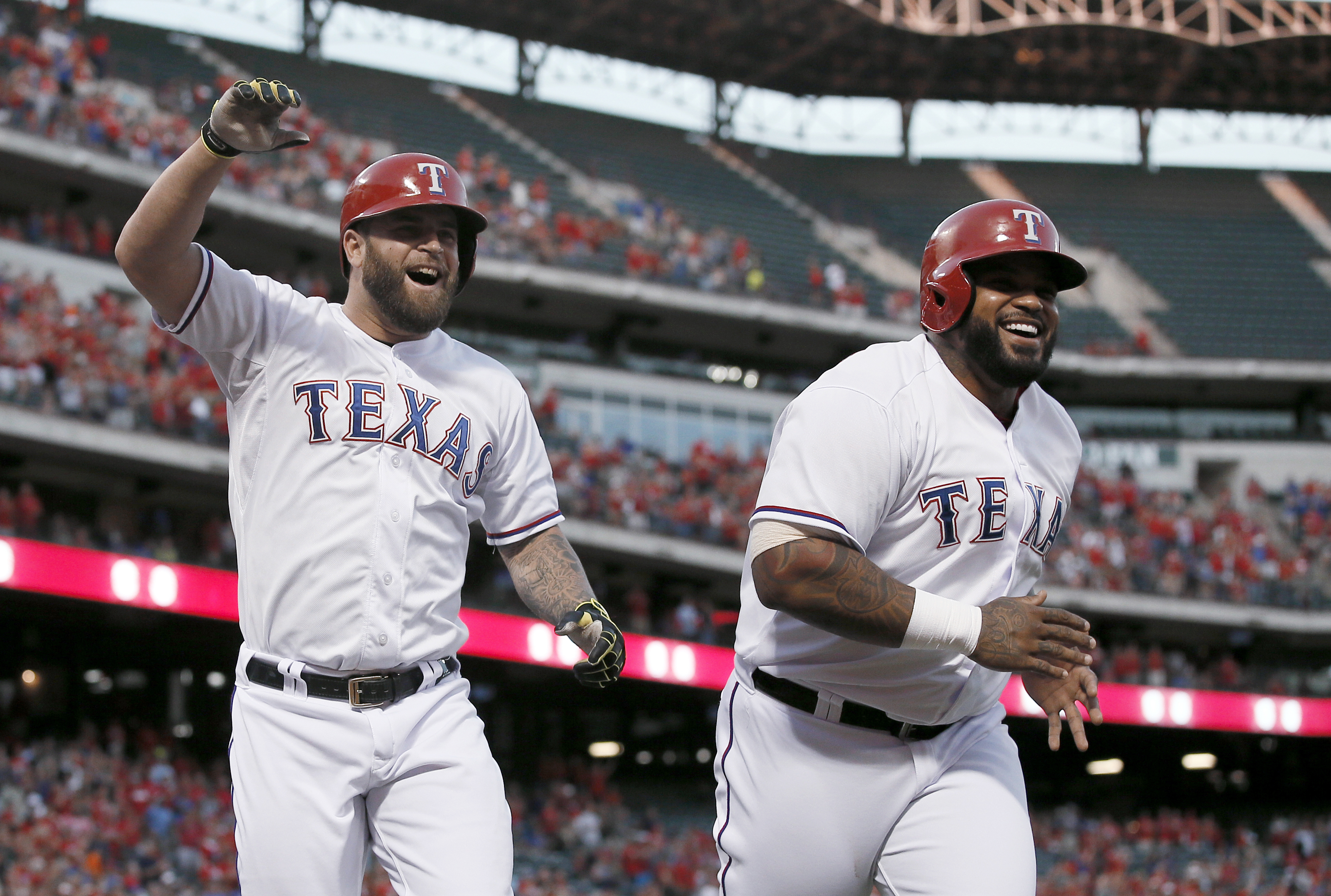 Texas Rangers' Mike Napoli, left, and Prince Fielder, right, celebrate a three-run home run by Napoli off Houston Astros' Dallas Keuchel during the first inning of a baseball game Wednesday, Sept. 16, 2015, in Arlington, Texas. The shot scored Fielder and
