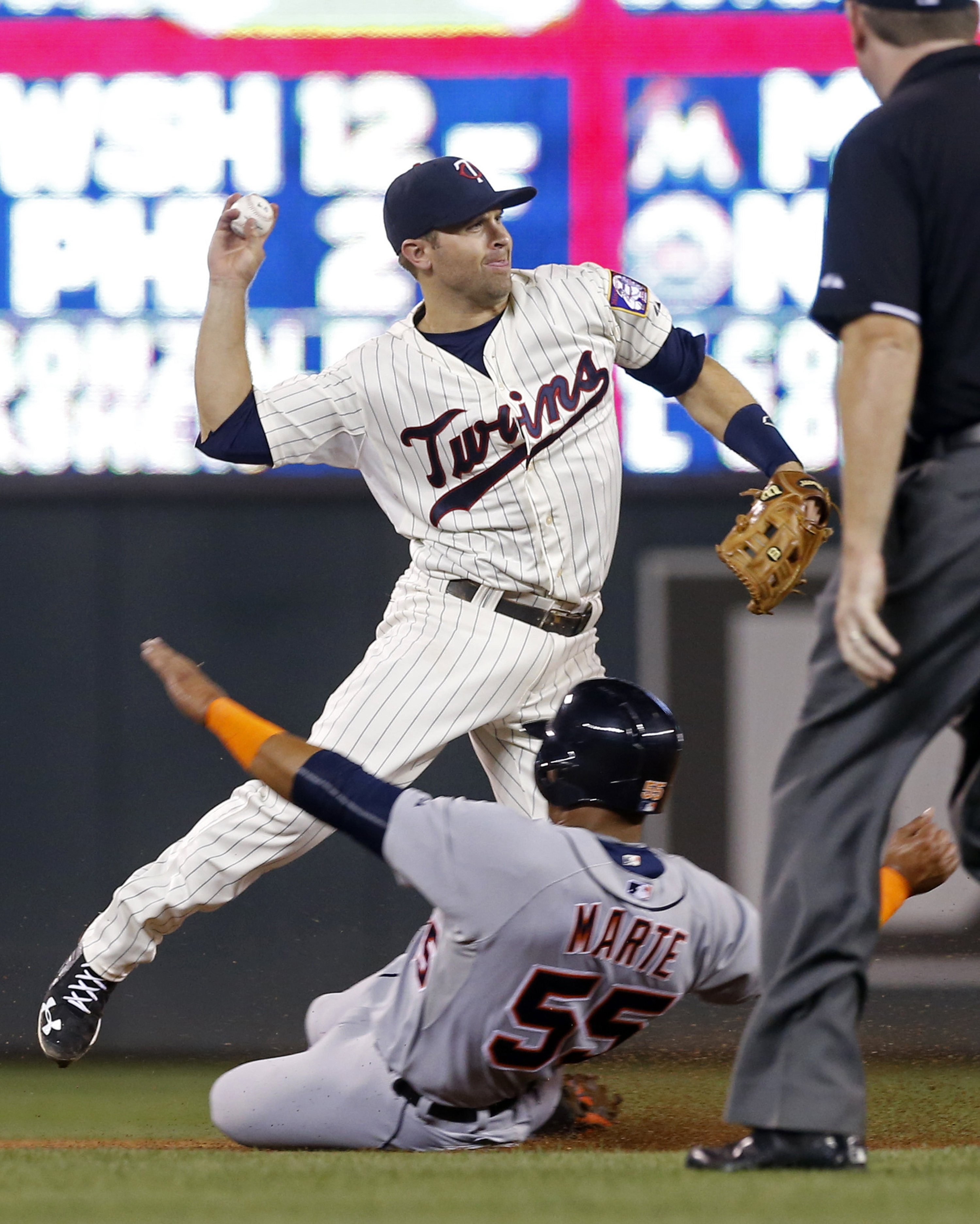 Minnesota Twins second baseman Brian Dozier throws to complete the double play on Detroit Tigers' James McCann after the force at second of Jefry Marte, bottom, in the fourth inning of a baseball game, Wednesday, Sept. 16, 2015, in Minneapolis. (AP Photo/