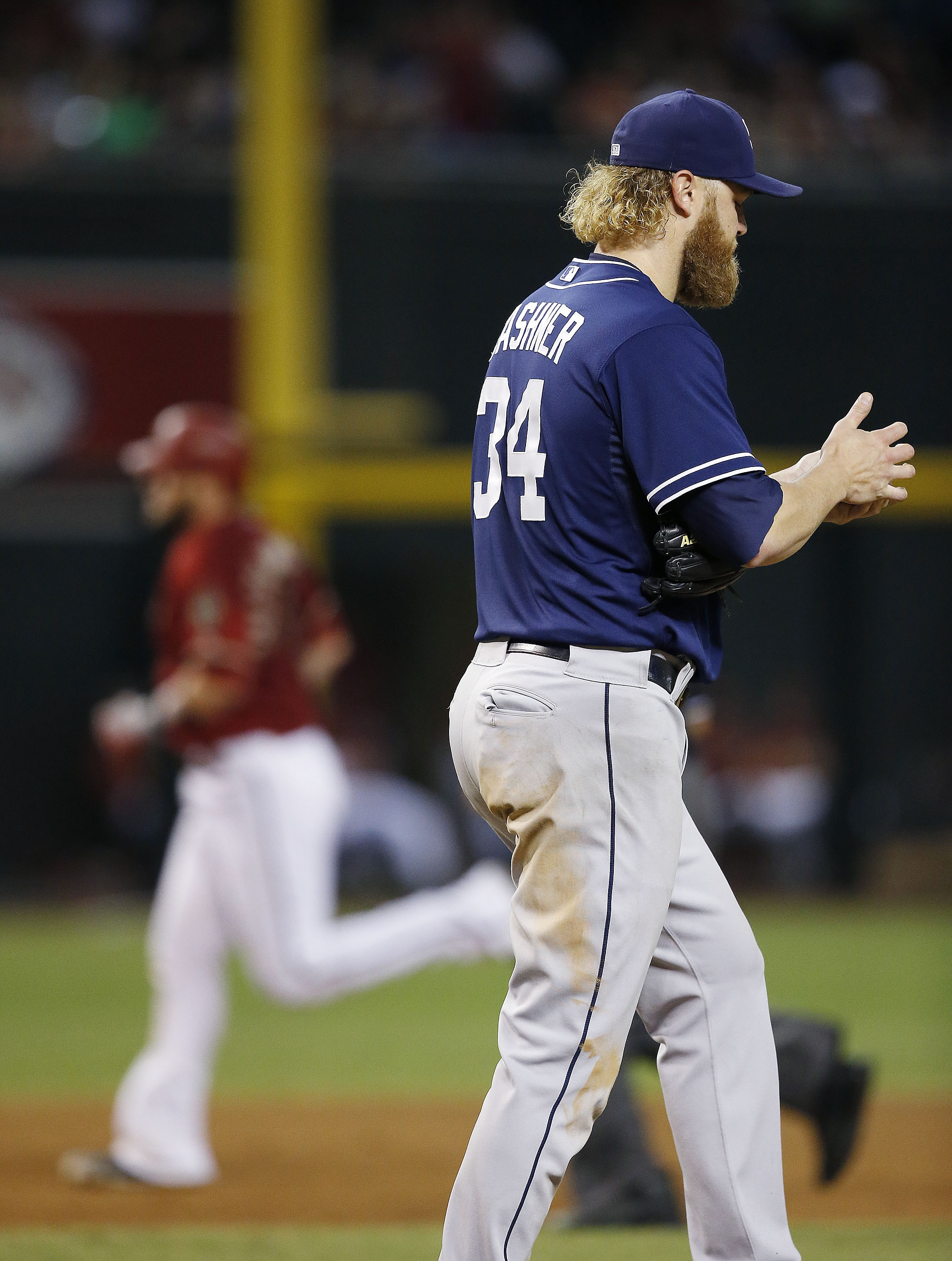 San Diego Padres' Andrew Cashner (34) rubs up a new baseball after giving up a home run to Arizona Diamondbacks' Jarrod Saltalamacchia, left, during the sixth inning of a baseball game Wednesday, Sept. 16, 2015, in Phoenix. (AP Photo/Ross D. Franklin)