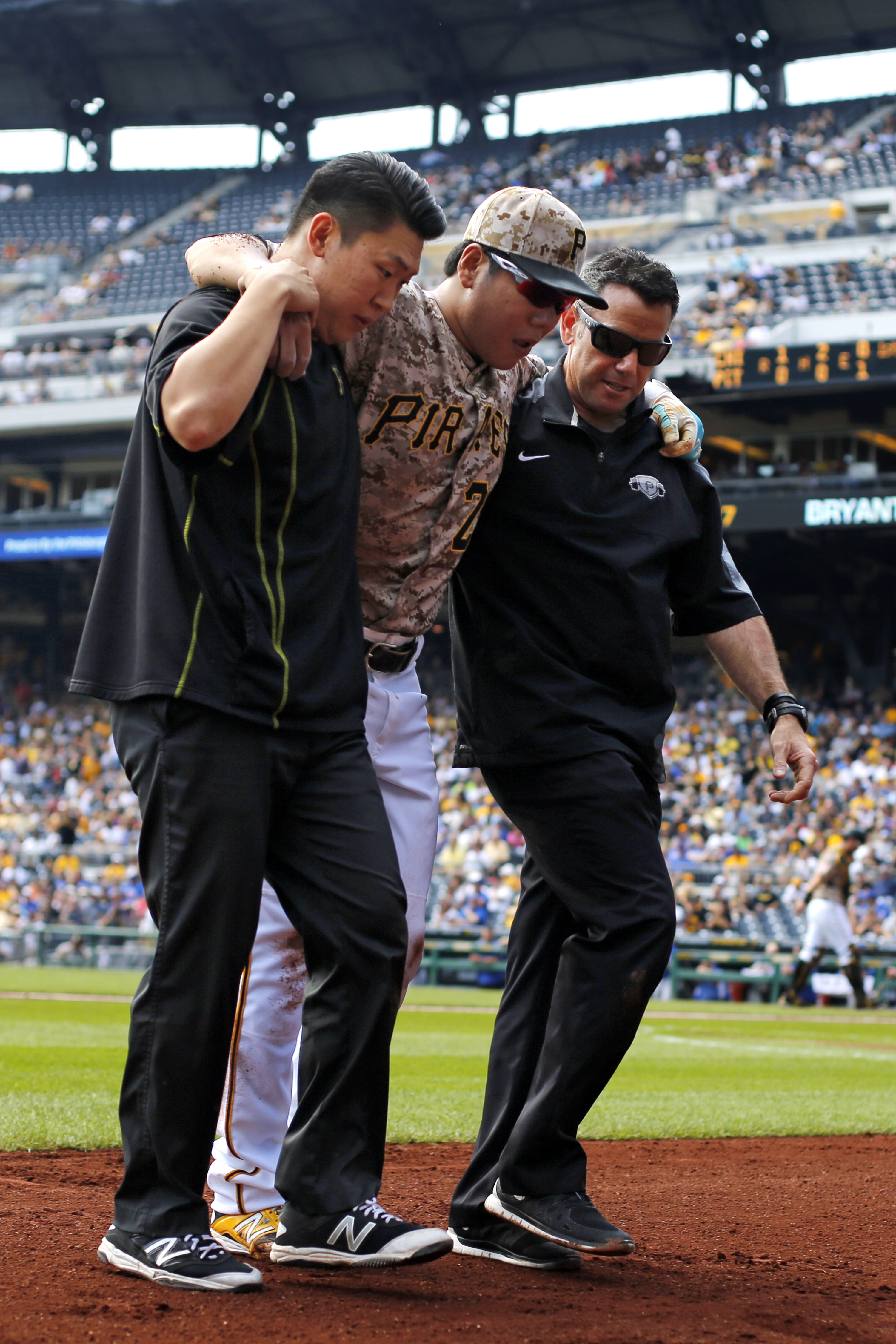 Pittsburgh Pirates' Jung Ho Kang, center, is helped off the field by a team trainer, right, and his interpreter after injuring his left leg turning a double play in the first inning of a baseball game against the Chicago Cubs in Pittsburgh, Thursday, Sept