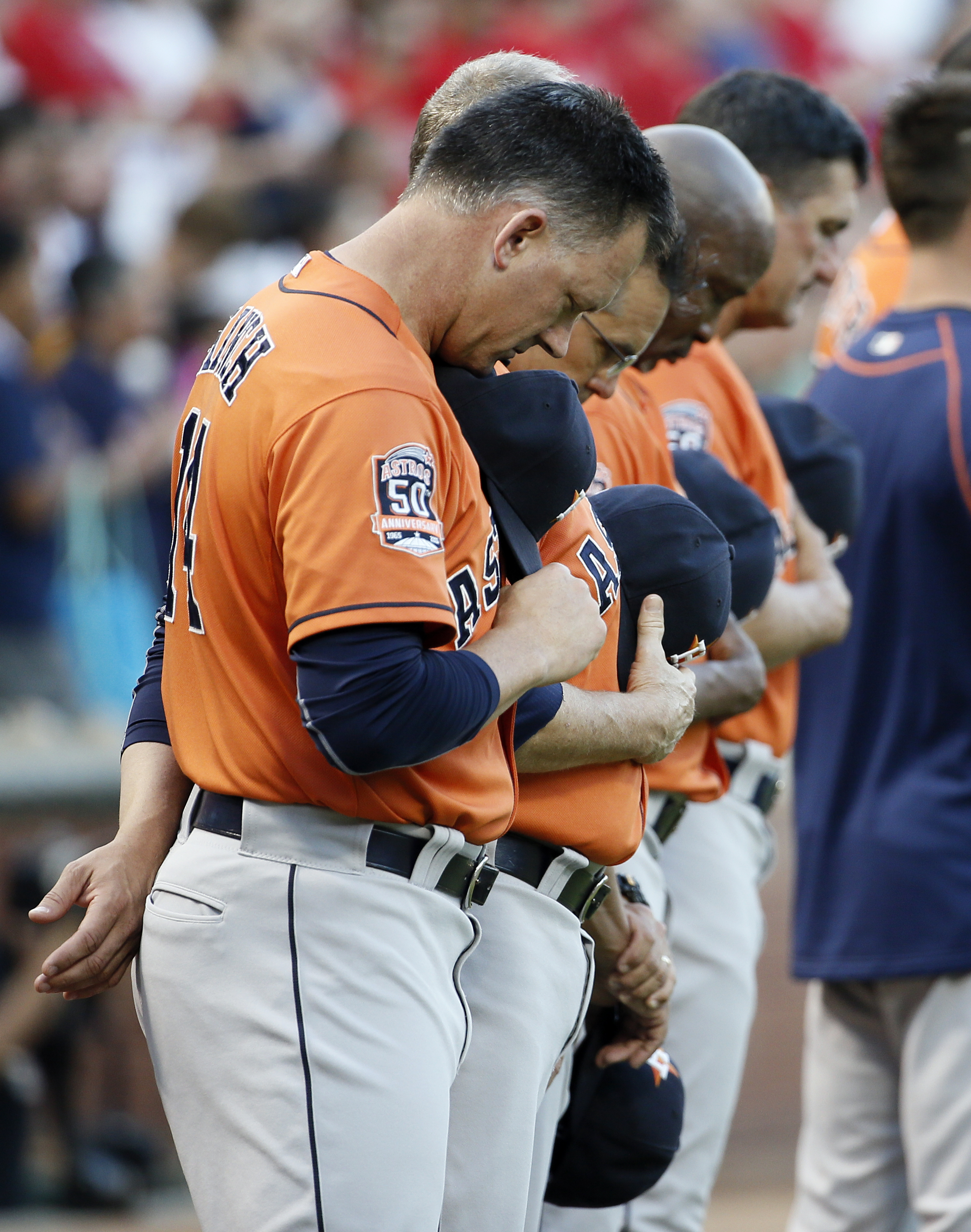 Houston Astros manager A.J. Hinch, front, and his staff bow their heads during a moment of silence in observance of the passing of baseball radio announcer Milo Hamilton, before the Astros' game against the Texas Rangers on Thursday, Sept. 17, 2015, in Ar