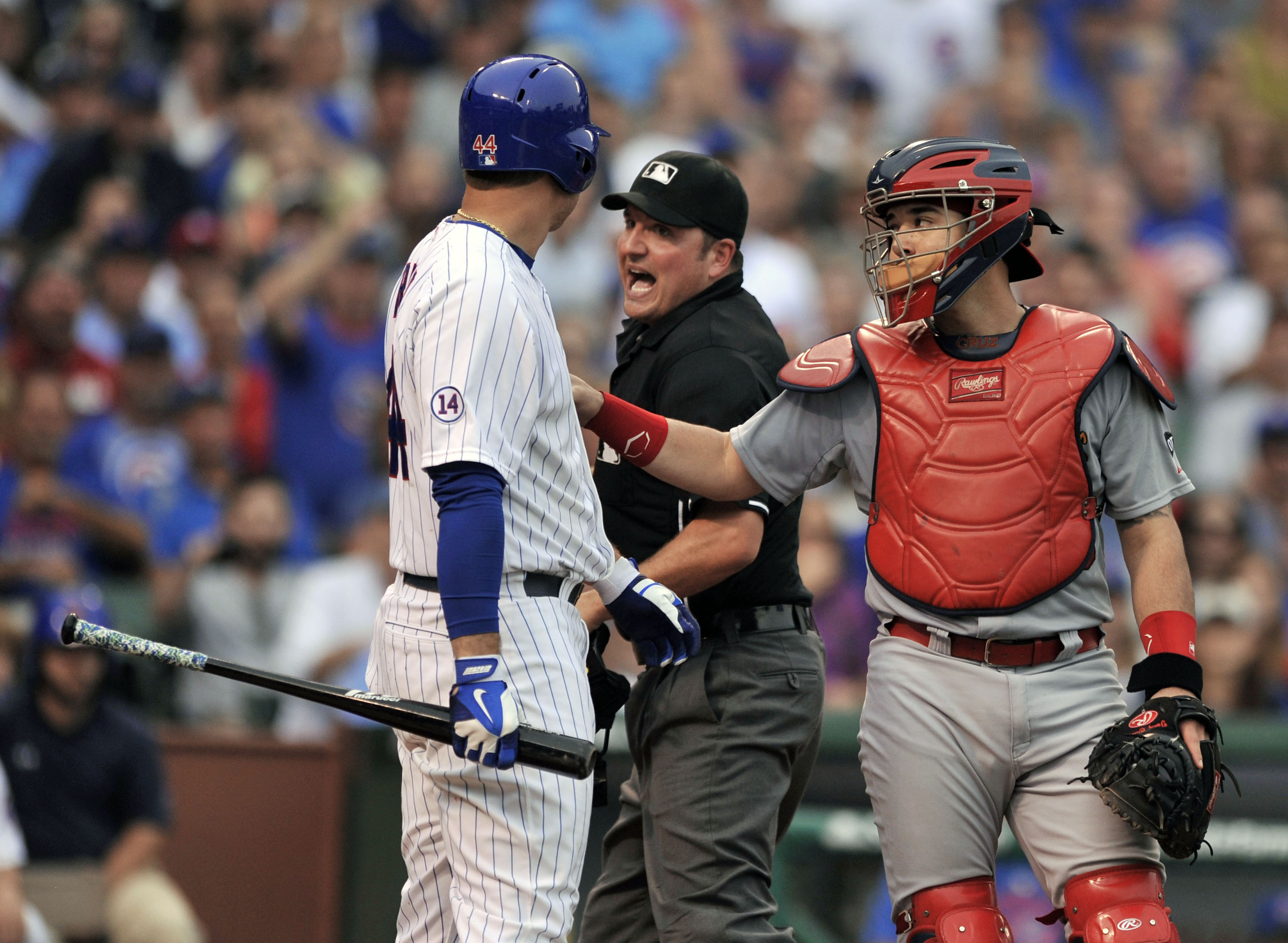 Chicago Cubs' Anthony Rizzo (44), argues with home plate umpire Dan Bellino after being hit by a pitch while St. Louis Cardinals catcher Tony Cruz (48), holds Rizzo back from charging the mound during the seventh inning of a baseball game Friday, Sept. 18