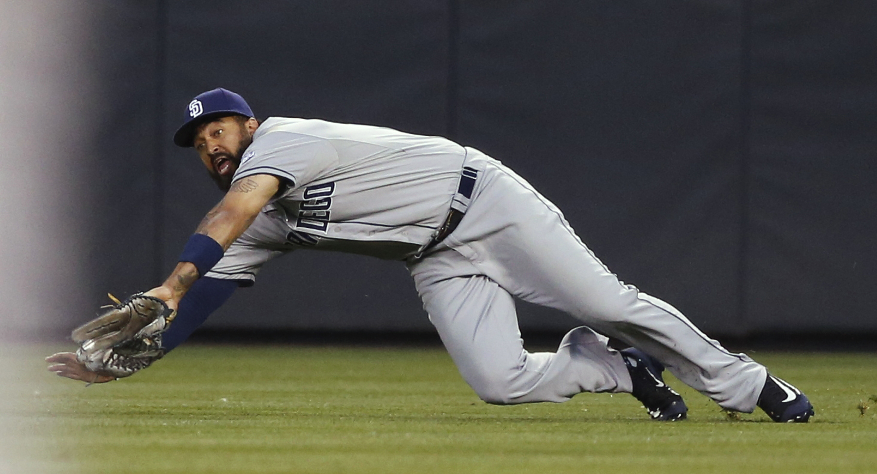 San Diego Padres right fielder Matt Kemp dives to catch a pop fly by Colorado Rockies' Carlos Gonzalez to end the bottom of the first inning of a baseball game Friday, Sept. 18, 2015, in Denver. (AP Photo/David Zalubowski)
