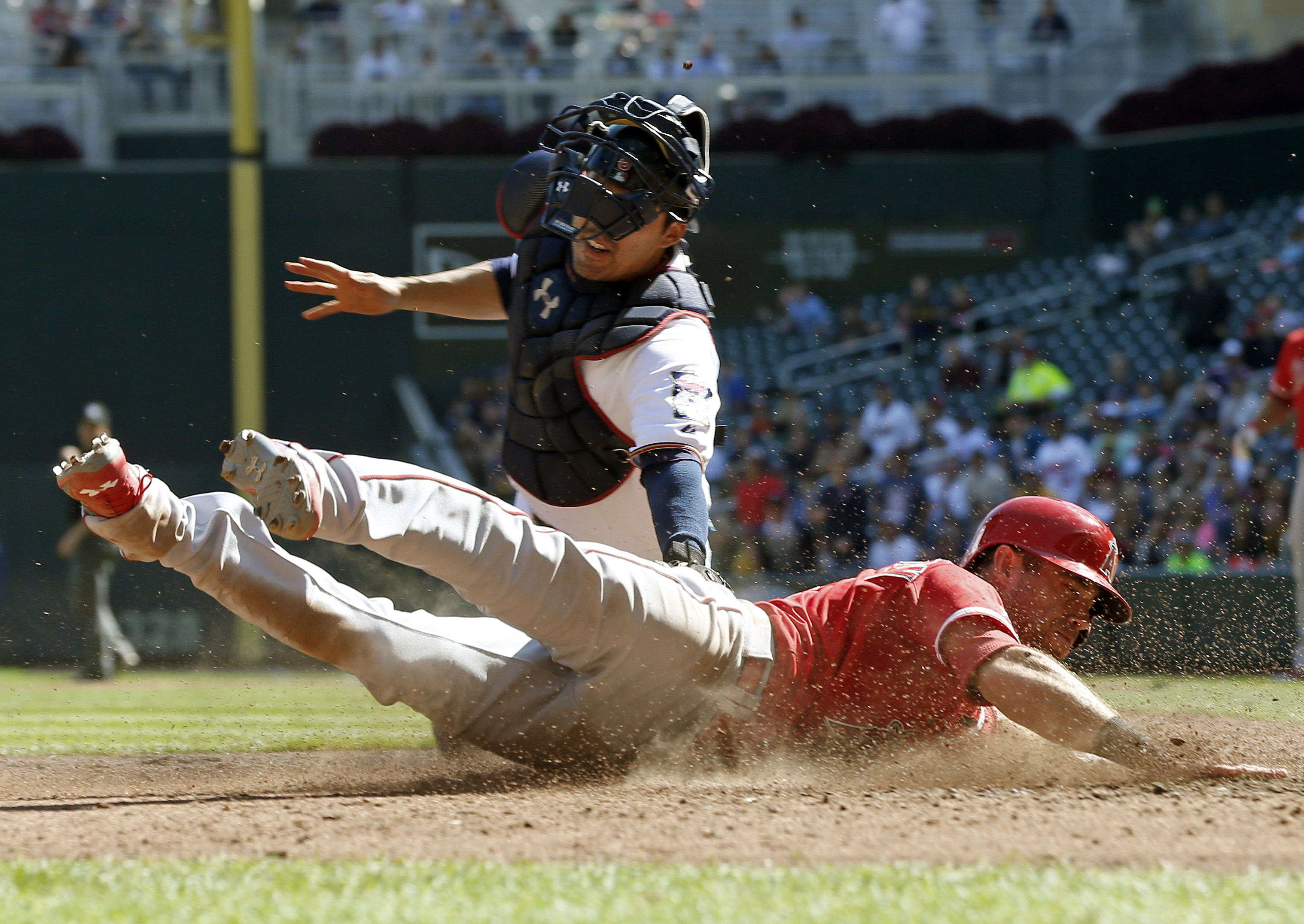 Los Angeles Angels' Taylor Featherston, right, beats the tag by Minnesota Twins catcher Kurt Suzuki to score in the sixth inning of Game 1 of a split doubleheader baseball game, Saturday, Sept. 19, 2015, in Minneapolis. (AP Photo/Jim Mone)