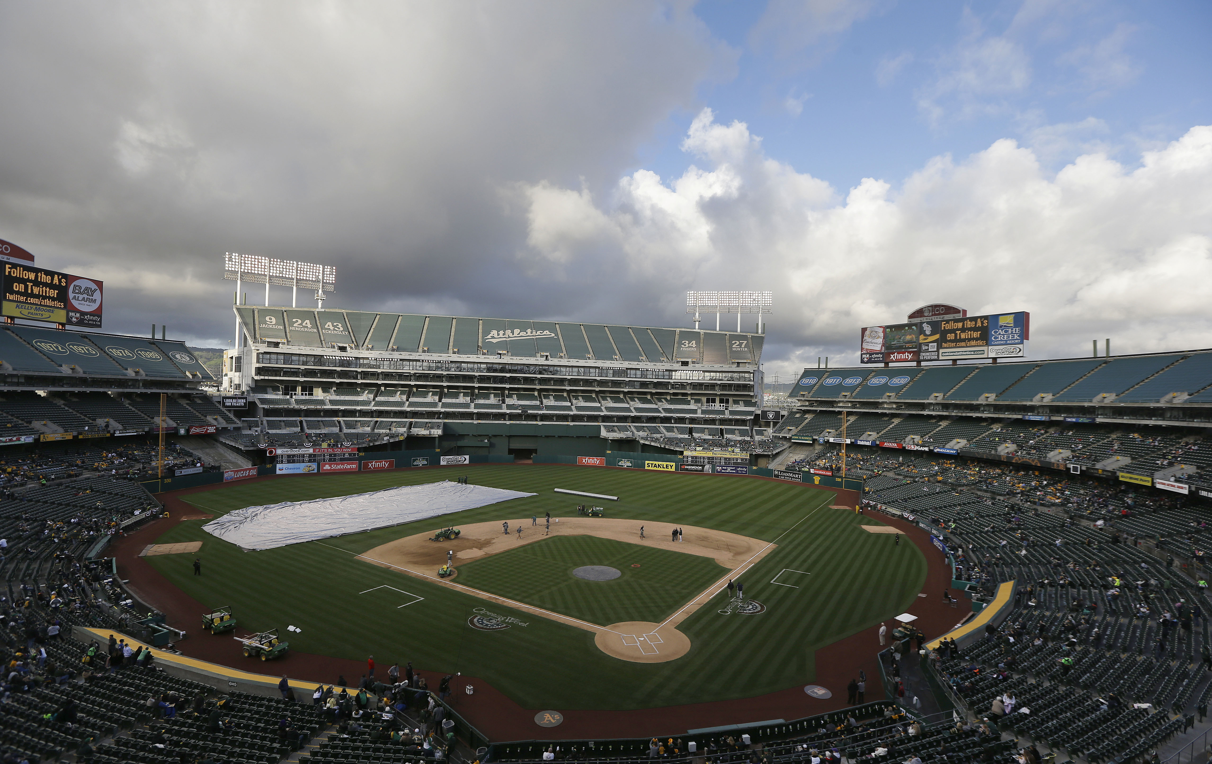 Members of the grounds crew work on the infield at O.co Coliseum before a baseball game between the Oakland Athletics and the Seattle Mariners in Oakland, Calif., Friday, April 4, 2014. The game has been delayed for weather related conditions to the infie