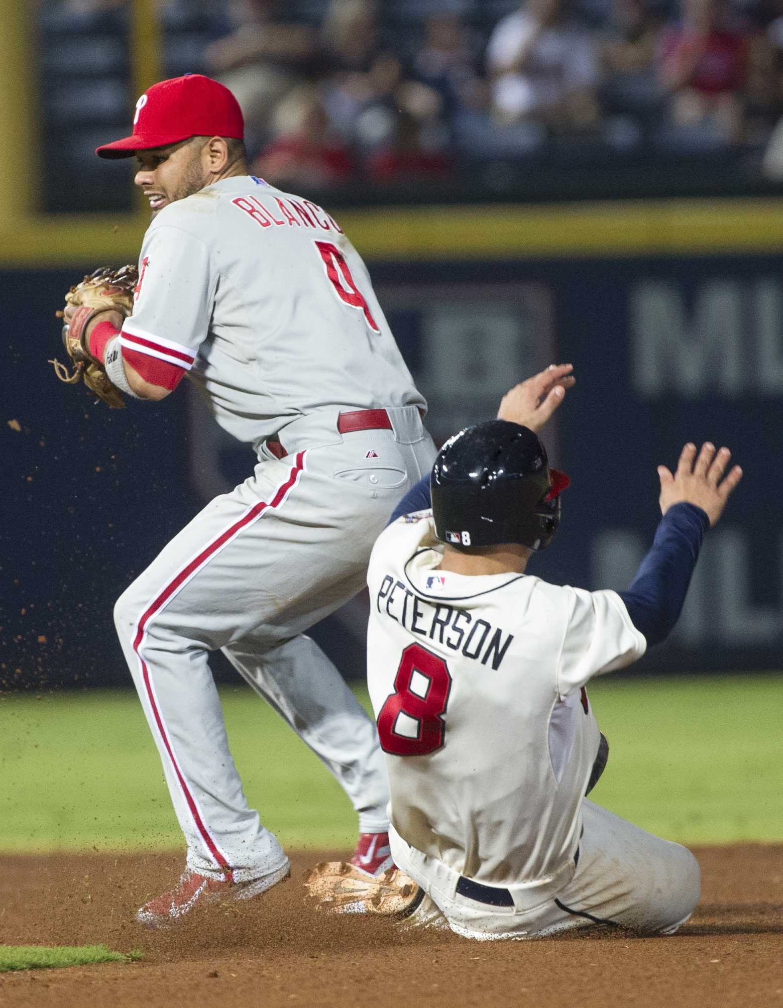 Philadelphia Phillies shortstop Andres Blanco forces out Atlanta Braves' Jace Peterson (8) while turning a double play on a Michael Bourne bunt during the seventh inning of a baseball game, Saturday, Sept. 19, 2015, in Atlanta. (AP Photo/John Amis)