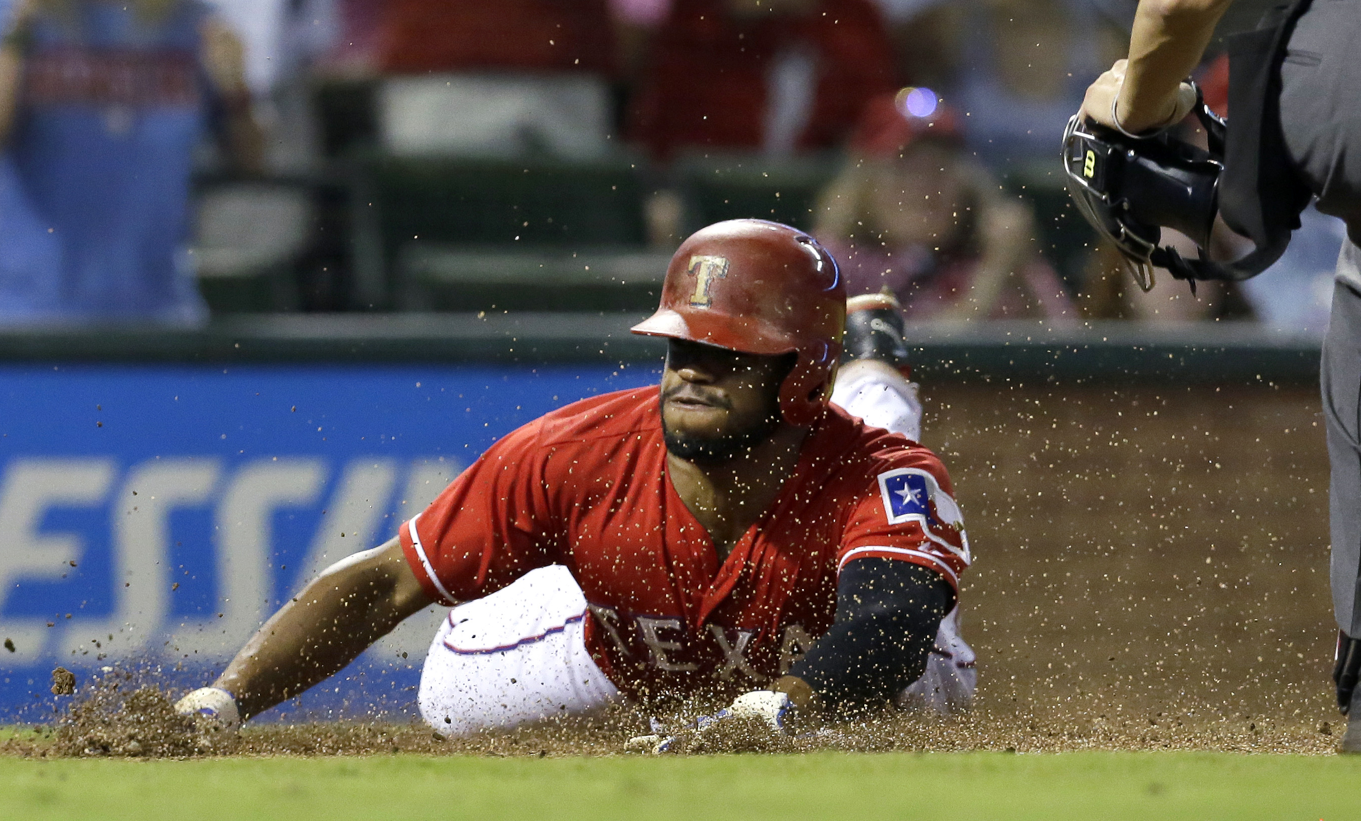 Texas Rangers' Delino DeShields slides into home plate to score on a double by teammate Adrian Beltre during the fourth inning of a baseball game against the Seattle Mariners in Arlington, Texas, Saturday, Sept. 19, 2015. (AP Photo/LM Otero)
