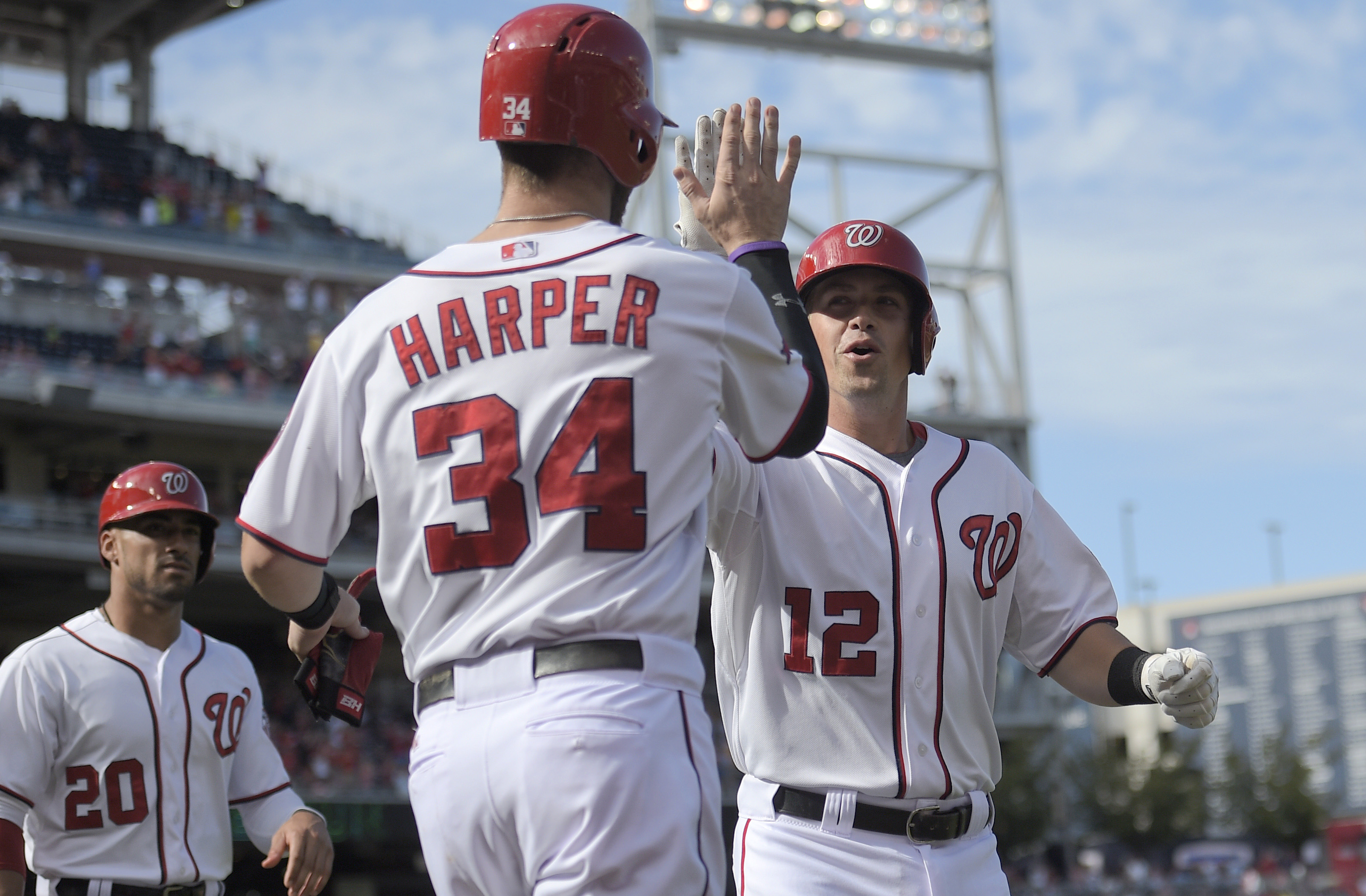 Washington Nationals' Tyler Moore (12) celebrates his three-run home run with Bryce Harper (34) during the sixth inning of a baseball game against the Miami Marlins, Sunday, Sept. 20, 2015, in Washington. Also seen is Washington Nationals' Ian Desmond. (A