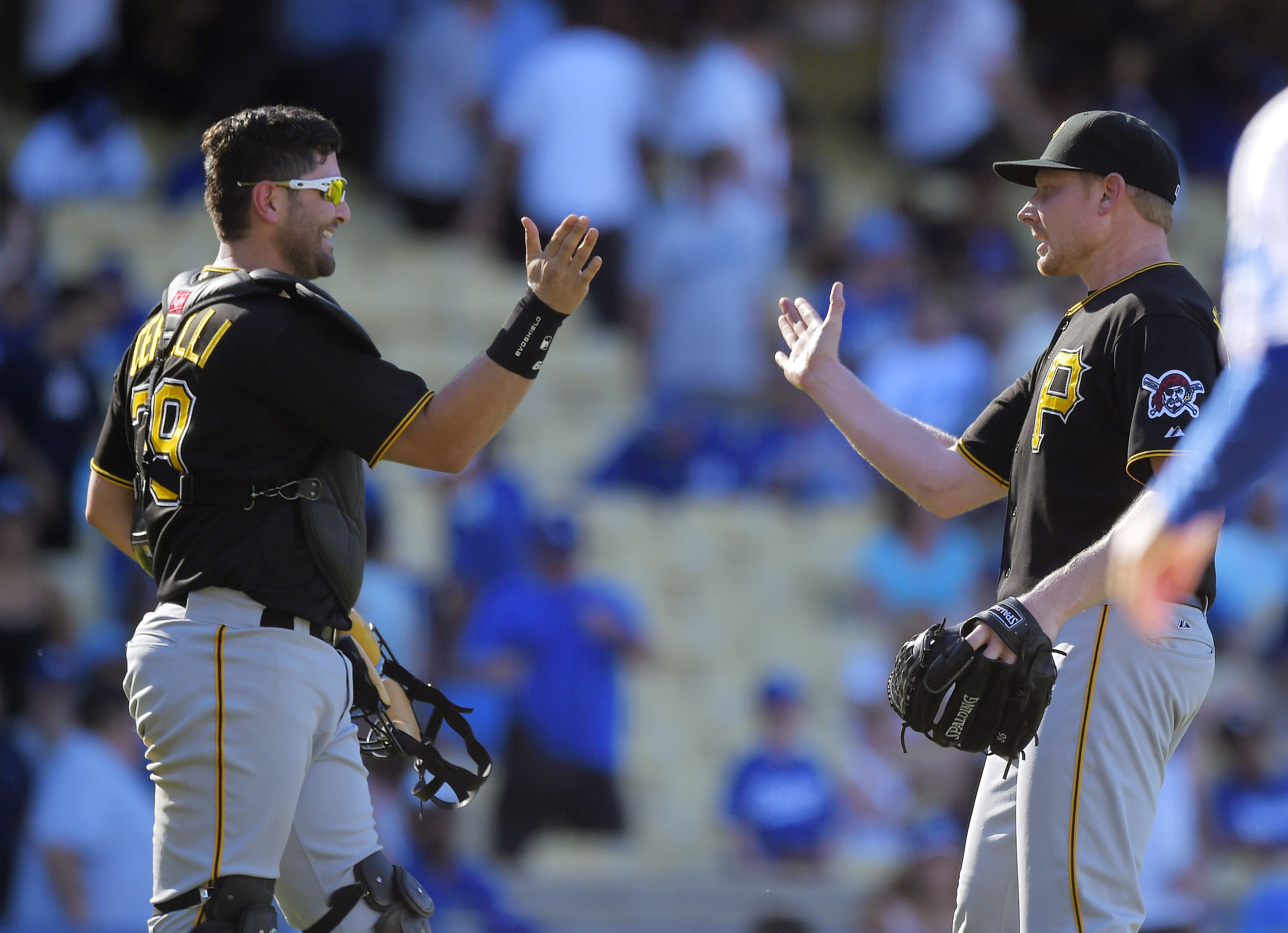 Pittsburgh Pirates relief pitcher Mark Melancon, right, and catcher Francisco Cervelli congratulate each other as the Pirates defeated the Los Angeles Dodgers 4-3 in a baseball game, Sunday, Sept. 20, 2015, in Los Angeles. (AP Photo/Mark J. Terrill)