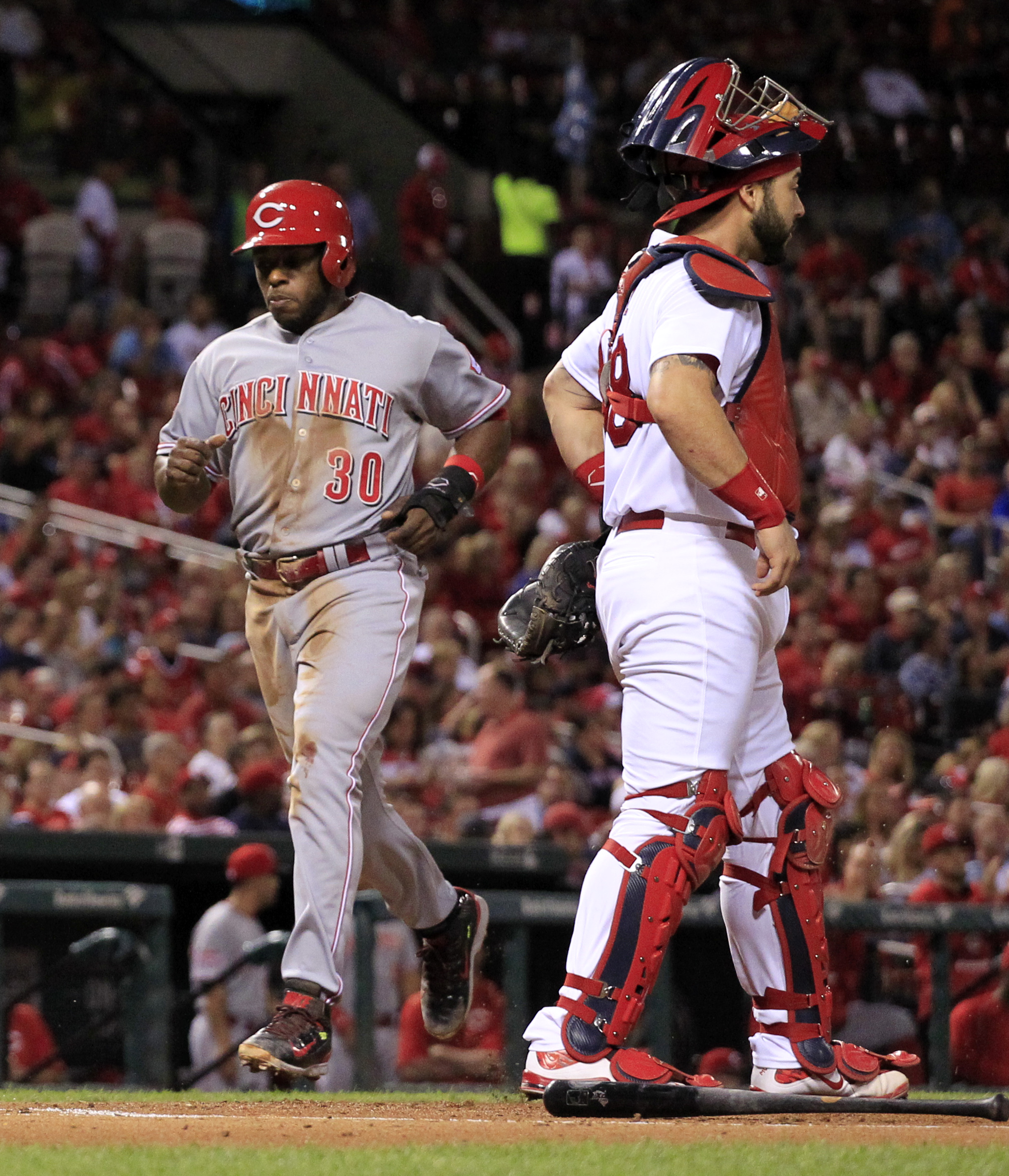 Cincinnati Reds' Jason Bourgeois, left, scores past St. Louis Cardinals catcher Tony Cruz, right, on a single by Brandon Phillips during the first inning of a baseball game against the St. Louis Cardinals on Monday, Sept. 21, 2015, in St. Louis. (AP Photo