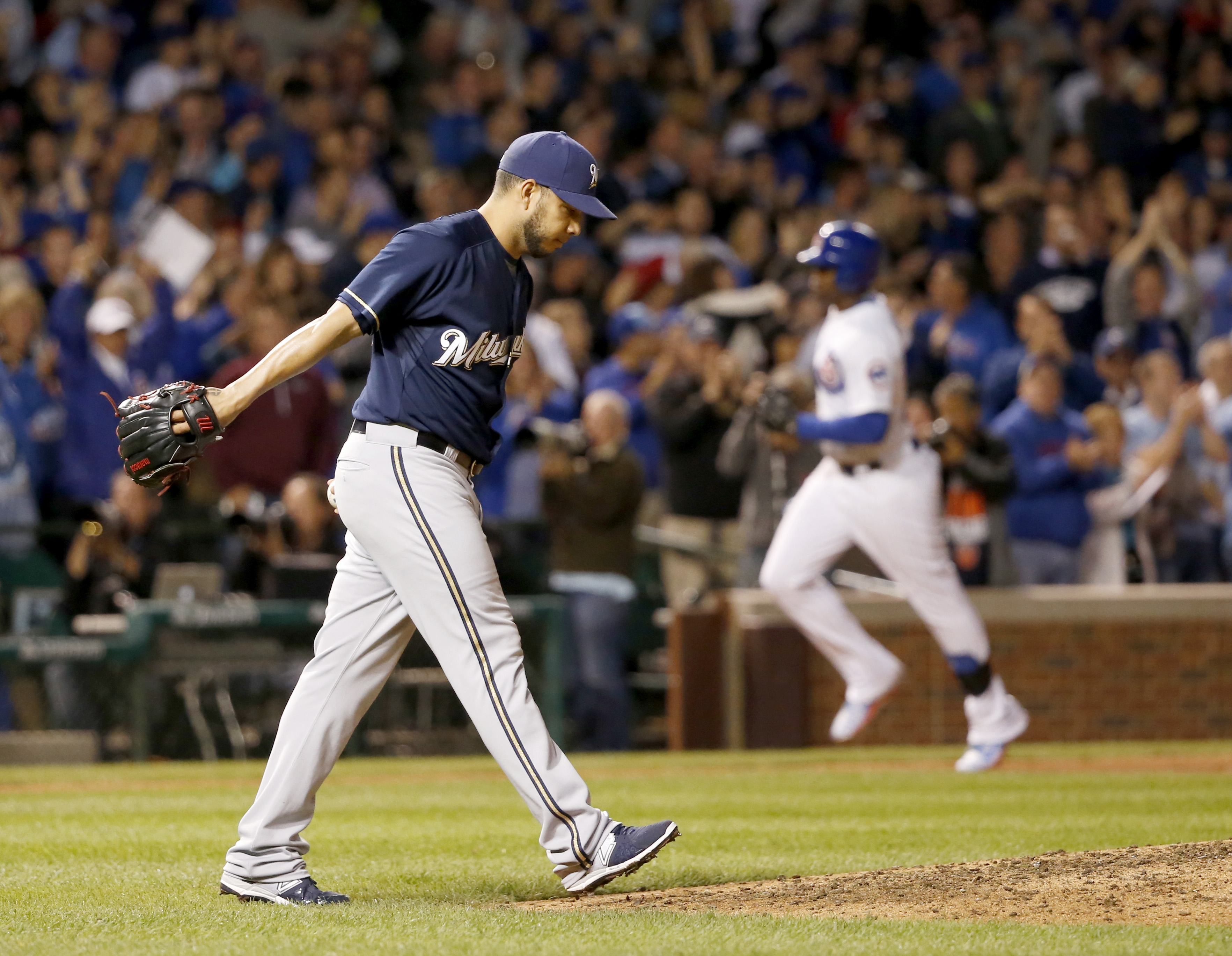 Milwaukee Brewers relief pitcher Cesar Jimenez returns to the mound after giving up a pinch hit, three-run home run to Chicago Cubs' Jorge Soler, right, also scoring Anthony Rizzo and Starlin Castro, during the seventh inning of a baseball game Monday, Se