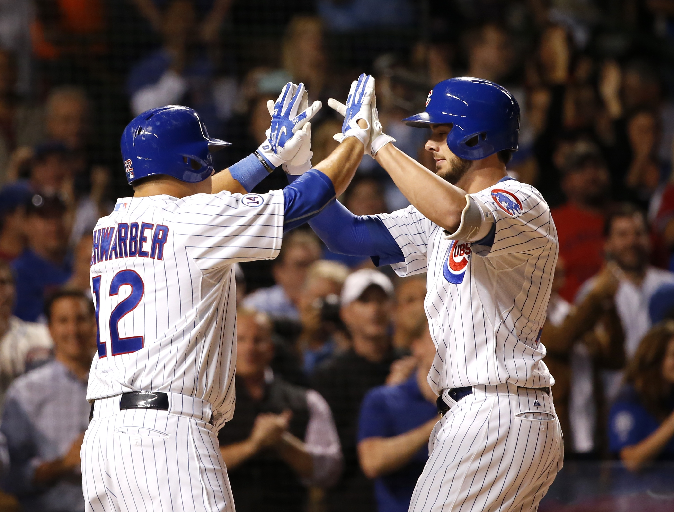 Chicago Cubs' Kris Bryant, right, celebrates with Kyle Schwarber after the pair scored on Bryant's two-run home run off Milwaukee Brewers starting pitcher Tyler Cravy during the third inning of a baseball game Tuesday, Sept. 22, 2015, in Chicago. (AP Phot