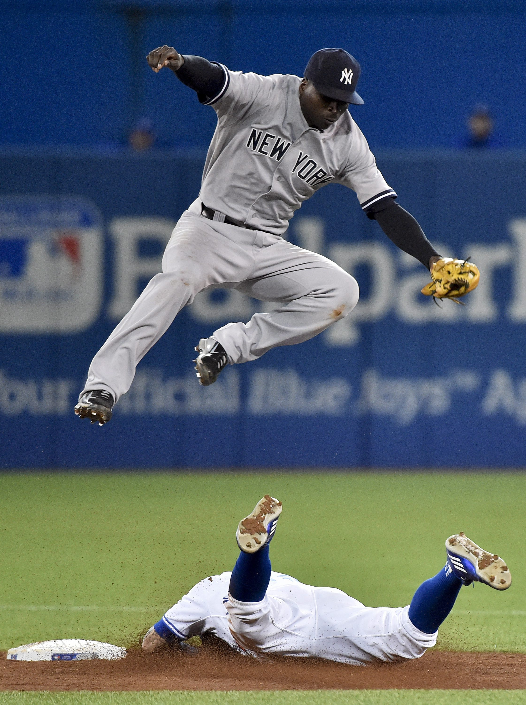 Toronto Blue Jays' Kevin Pillar, bottom, is safe after stealing second base past New York Yankees' shortstop Didi Gregorius during the fifth inning of a baseball game Tuesday, Sept. 22, 2015, in Toronto. (Nathan Denette/The Canadian Press via AP) MANDATOR